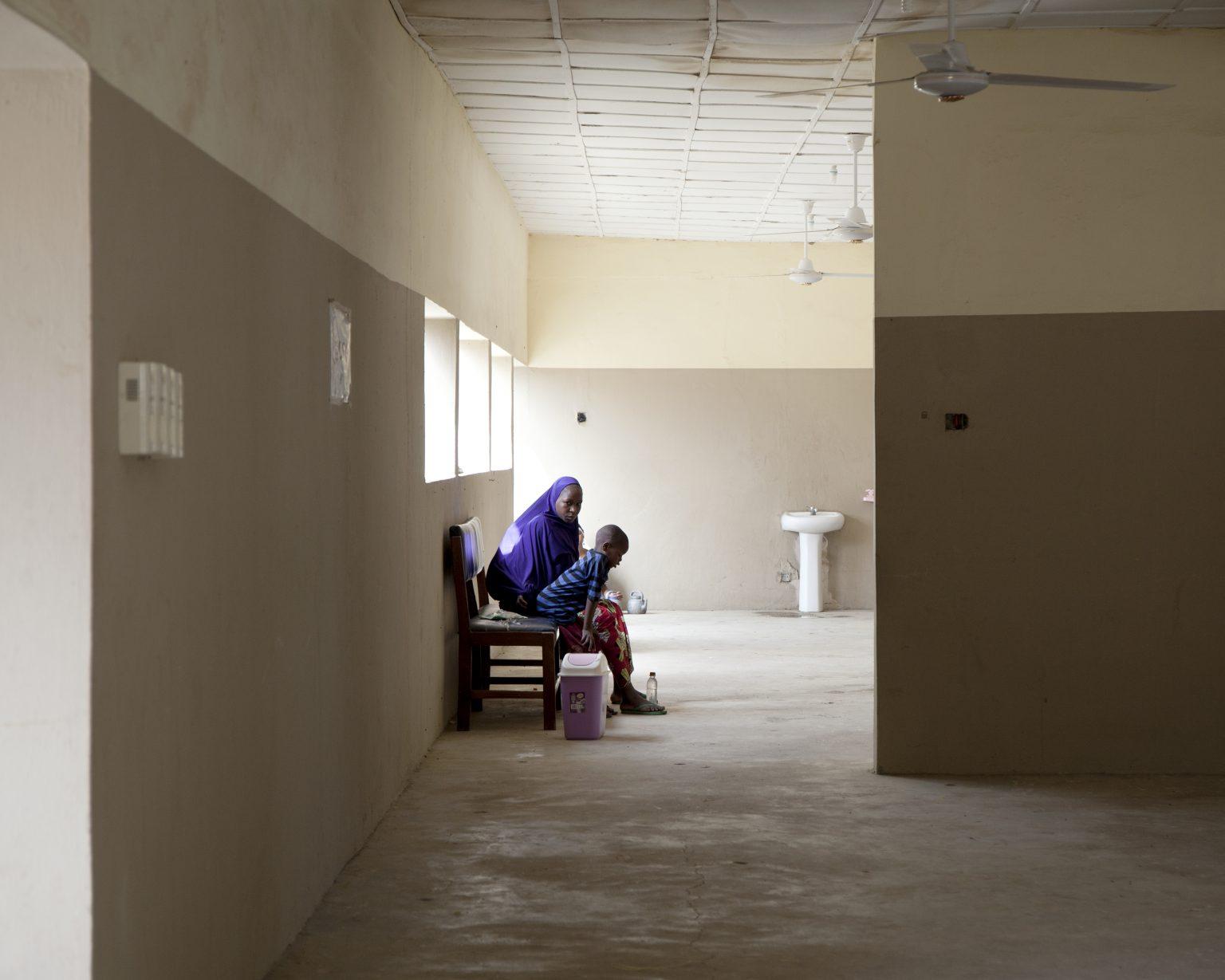 Ngala, Borno State (Nigeria). A woman with her child in the general hospital, next to the large camp for displaced people called Arabic Camp. Before the attack of Boko Haram, it was the main hospital in Ngala. >< Ngala, Stato di Borno (Nigeria). Una donna con il suo bambino dentro l'ospedale generale di Ngala, accanto al grande campo per gli sfollati chiamato Arabic Camp. Prima dell'attacco di Boko Haram era il principale ospedale di Ngala.