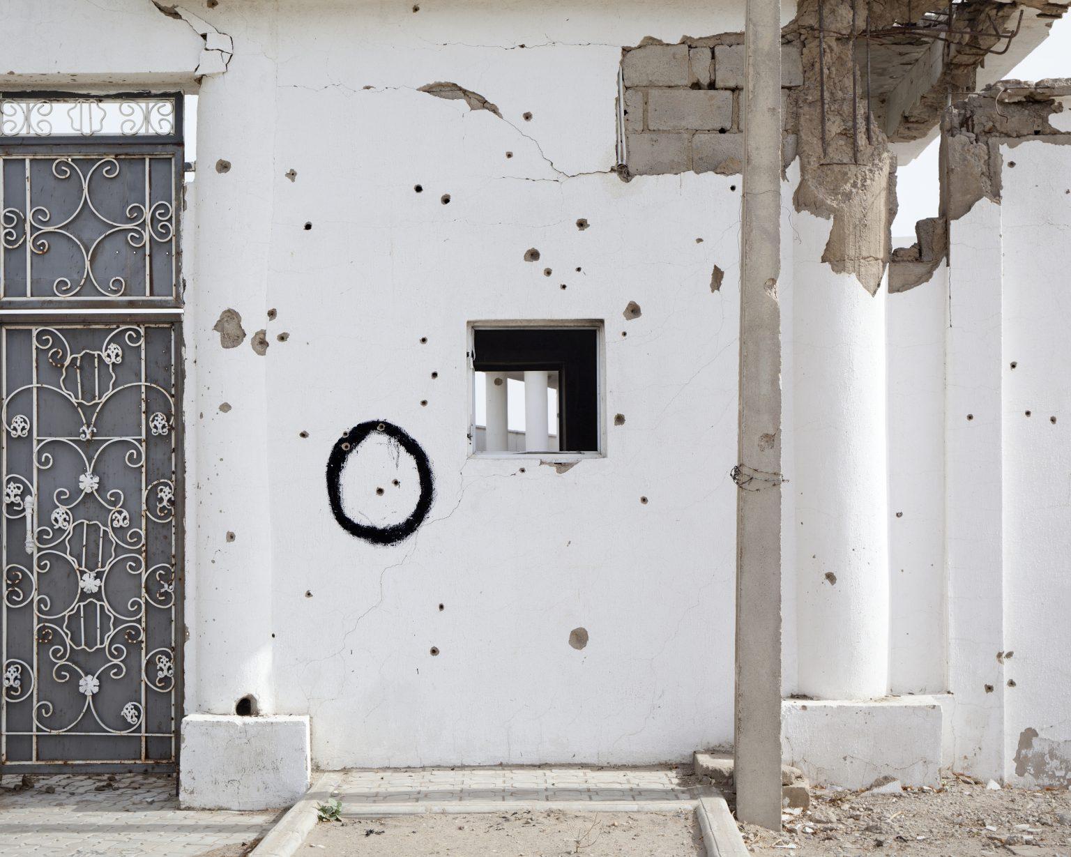 Gamboru Ngala, Borno State (Nigeria), May 2018 - Wall of a mosque riddled with bullets. In 2014 Gamboru was besieged by Boko Haram for 16 months. Today it is controlled by the Nigerian army but the area of Marte, with which it borders, is still occupied by the terrorist group. Approximately 89.000 people are displaced, including refugees from other areas of Borno and returnees from fleeing. >< Gamboru Ngala, Stato di Borno (Nigeria), maggio 2018 - Muro di una moschea crivellato di proiettili. Nel 2014 Gamboru è stata assediata da Boko Haram per 16 mesi. Oggi è controllata dall'esercito nigeriano ma l'area di Marte con cui confina è ancora occupata dal gruppo terroristico. Gli sfollati, tra rifugiati da altre zone del Borno e rientrati dalla fuga, sono circa 89.000.