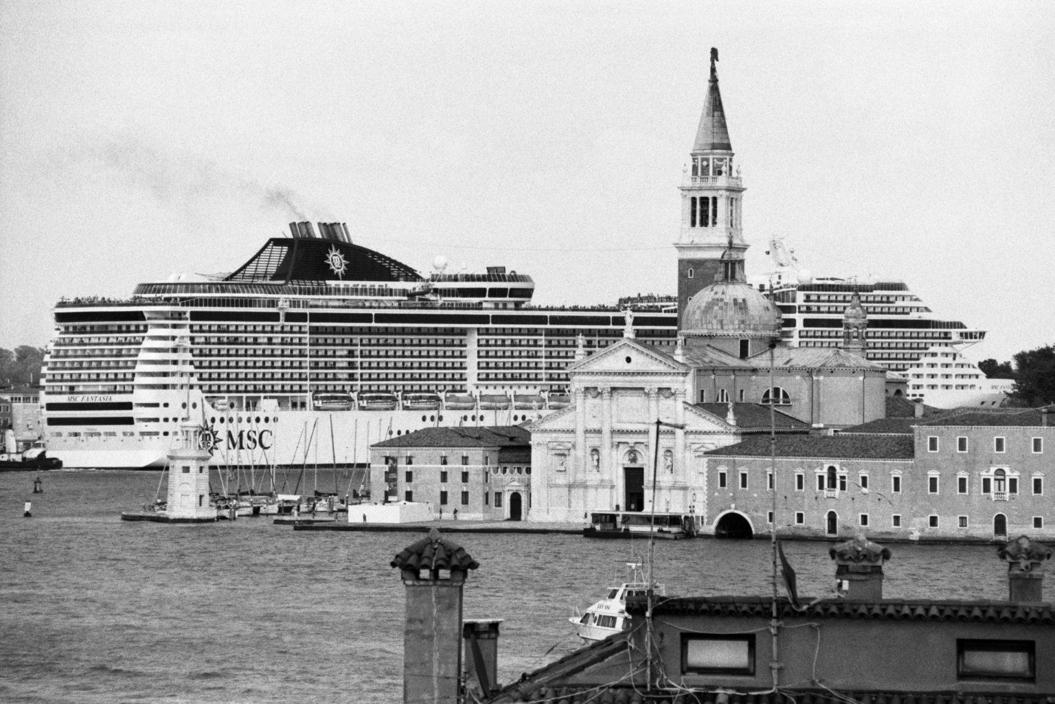 """Venice, August 2013 - Big cruise liners invade the city - MSC Fantasia cruise ship passing by the old town ><  Venezia, agosto 2013 - Le grandi navi da crociera invadono la città - La MSC Fantasia passa davanti al centro storico<p><span style=""""color: #ff0000""""><strong>*** SPECIAL   FEE   APPLIES ***</strong></span></p>*** SPECIAL   FEE   APPLIES *** *** Local Caption *** 00483759"""