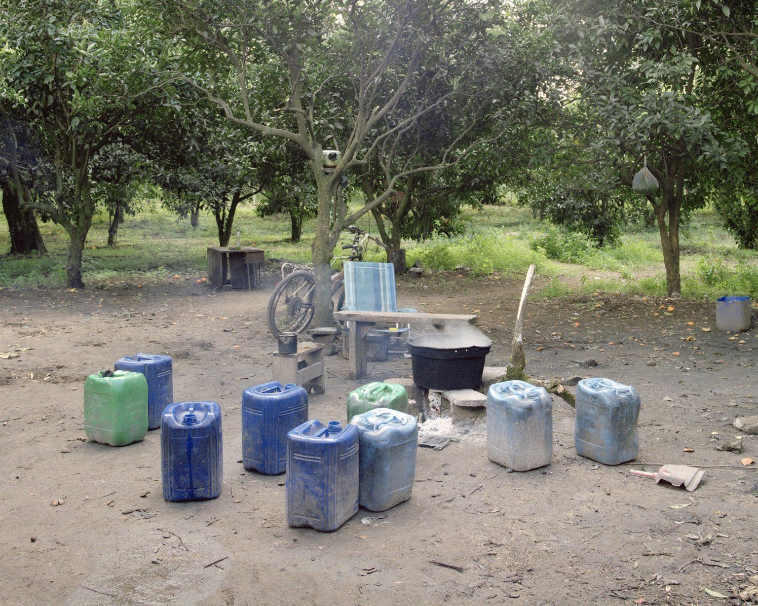 """Drosi (Gioia Tauro), 2016. Temporary kitchen set in a citrus grove in the plain of Gioia Tauro. According to CGIL (union organization) in Italy there are about 400 thousand foreign daily laboures who find work through the """"caporalato"""" (system of directly hiring farm labour for very low wages by landowner's agents). >< Drosi (Gioia Tauro), 2016. Cucina temporanea allestita in un agrumeto della piana di Gioia Tauro. Secondo la CGIL in Italia sono circa 400 mila i lavoratori stagionali stranieri che trovano lavoro attraverso il caporalato."""