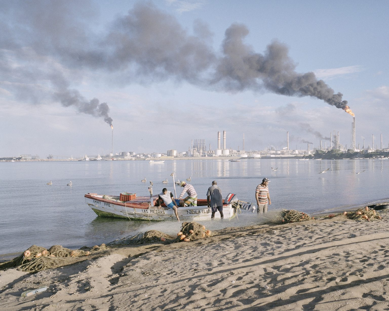 Fishermen coming back from the work session at the sun rise in Punta Cardon. In the background the biggest oil refinery of Venezuela.