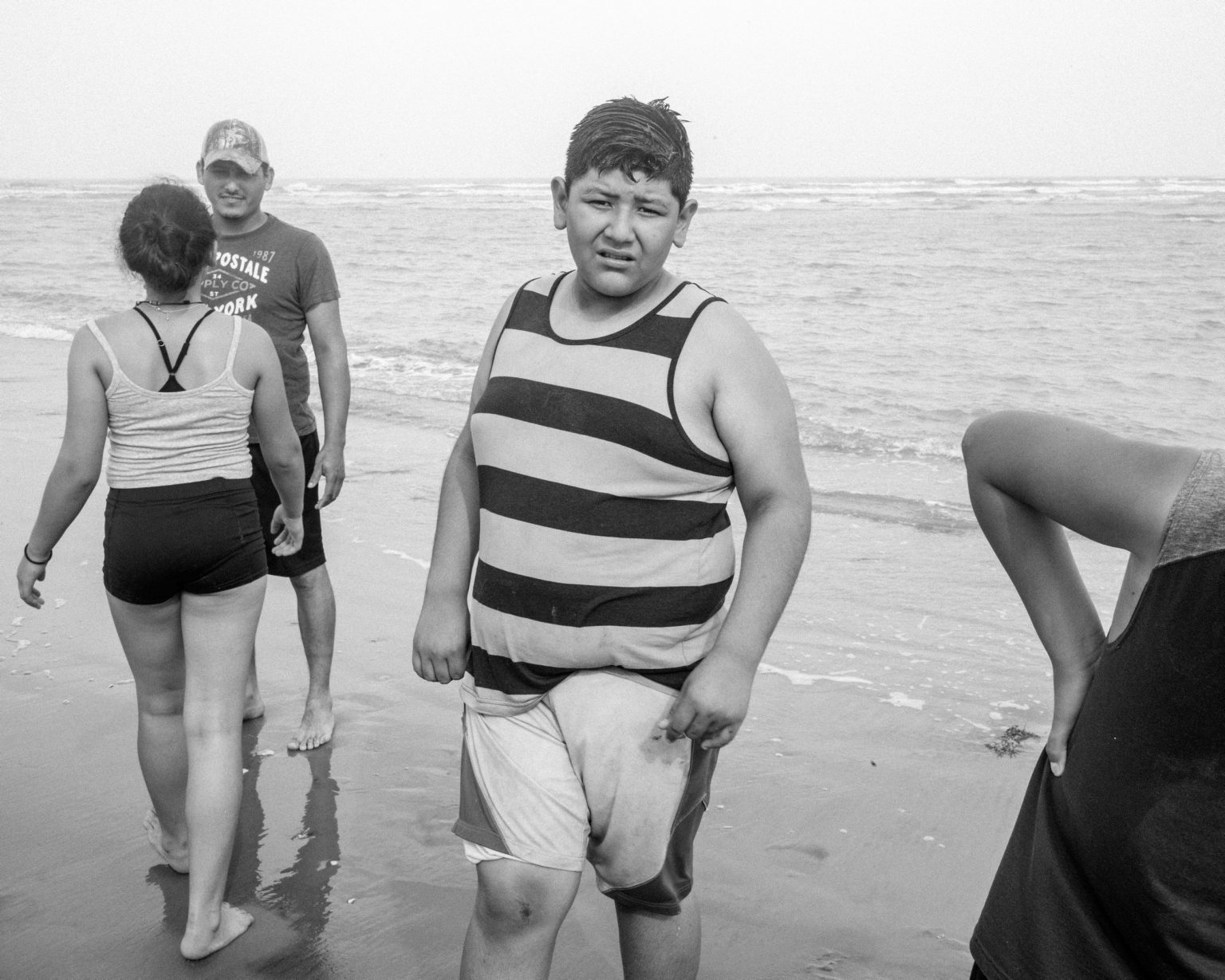 Family of migrants along the Rio Grande delta where Mexican families go to meet their relatives on the Mexican bank of the river. Brownsville, TX,