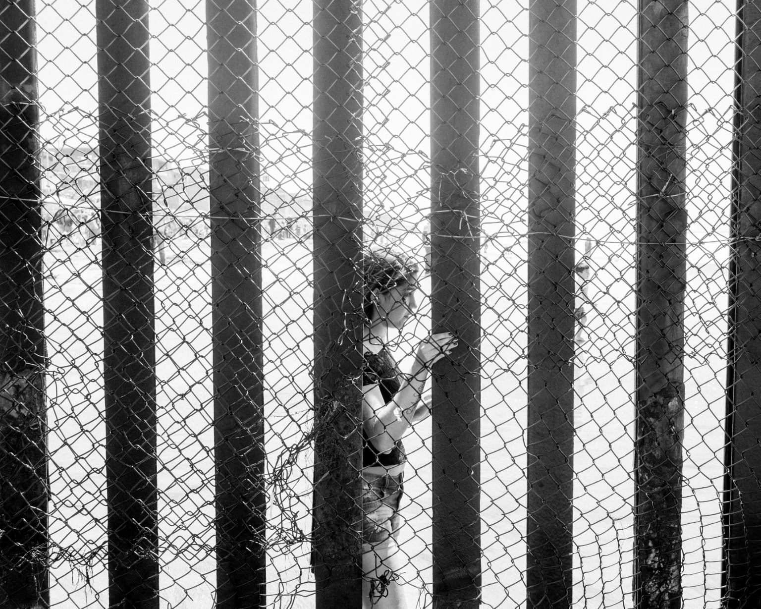 A mexican girl along the wall dividing the beaches of Tijuana and San Diego. CA.  April 2017.