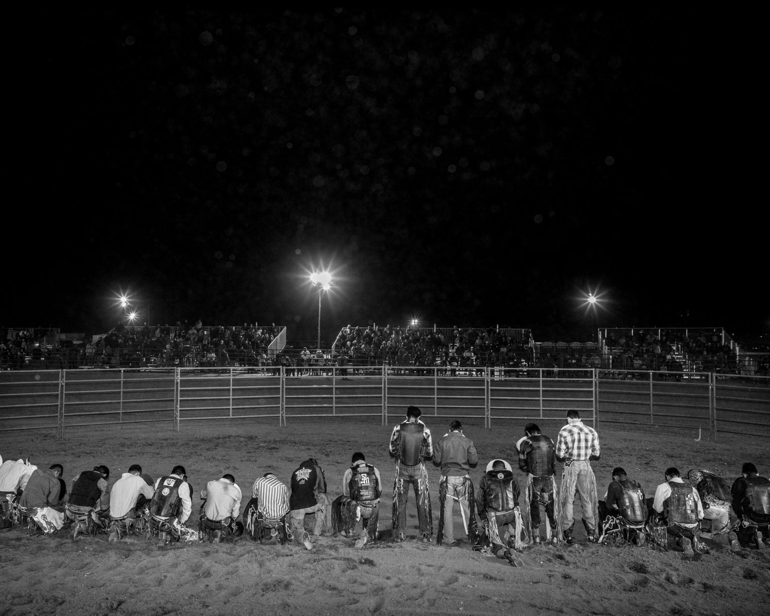Participants to a rodeo for the 10th anniversary of the Ak-Chin native reservation kneel down as the American himn plays. Maricopa, Arizona.