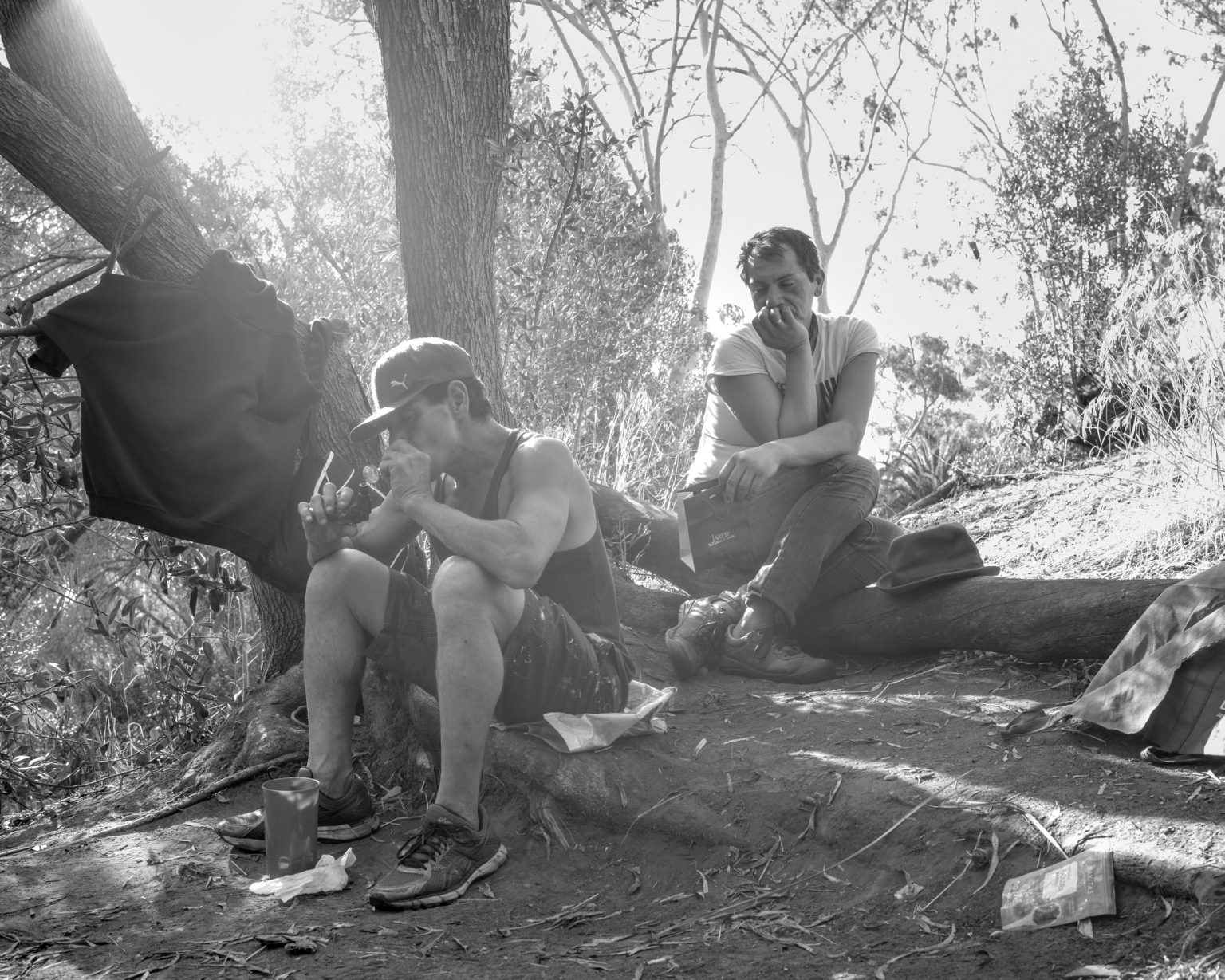 Pablo and Josè smoking crack in Balboa Park. Pablo says he managed to cross the border several months after the rest of his family and once he was in the US he realized his family began a new life without him. San Diego, California, November 2017.