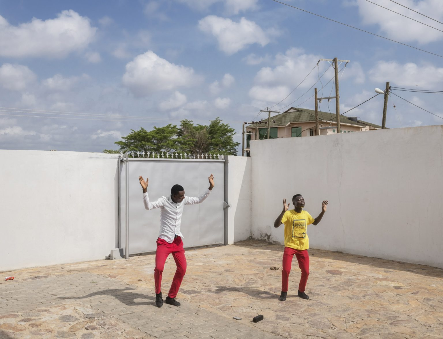 """Republic of Ghana, Greater Accra Region, April 2019: young worshipers dancing in the courtyard of Qodesh Family Church, The Qedesh, a Lighthouse Chapel International branch located in East Legon Hills and inaugurated in 2017.According to a Pew Research Center's report titled """"The Age Gap inReligionAround the World"""", Georgia and Ghana are the only two countries in the world where young people aged 18-39 are more religious than those aged 40 and above.*Stitched photograph*"""