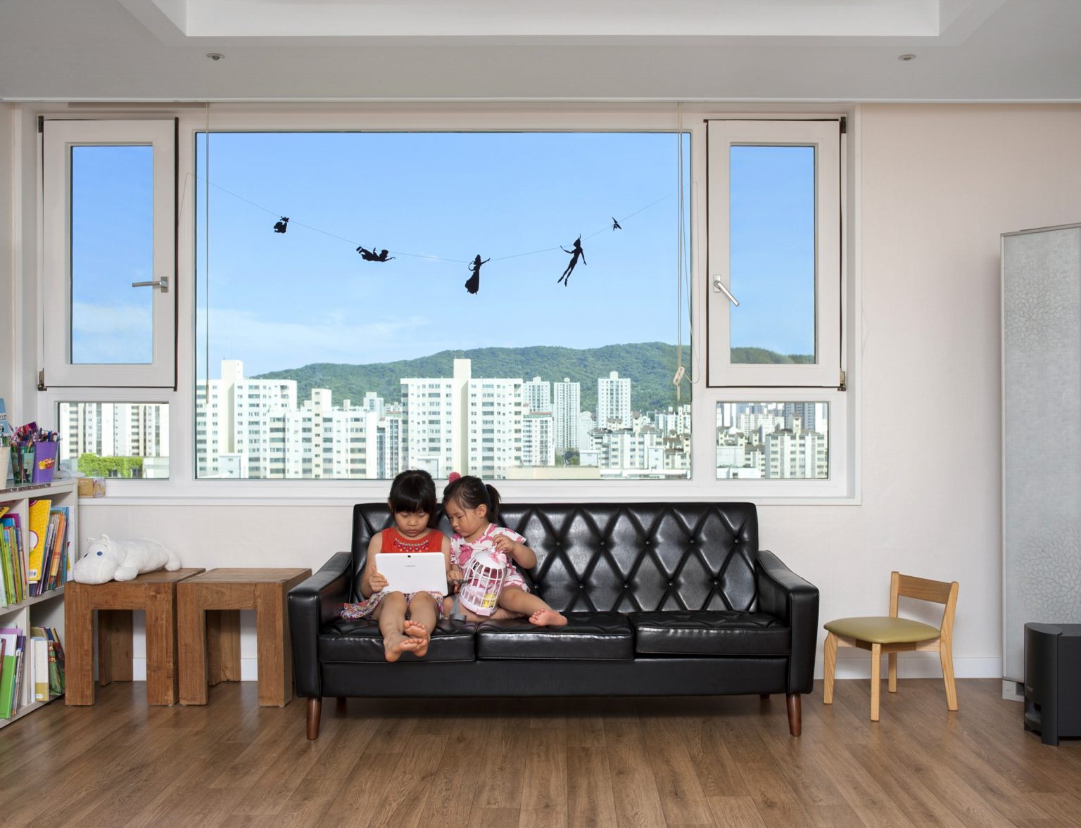 Republic of Korea, Seoul, July 2015: children watching a cartoon in their family apartment.*Stitched photograph*