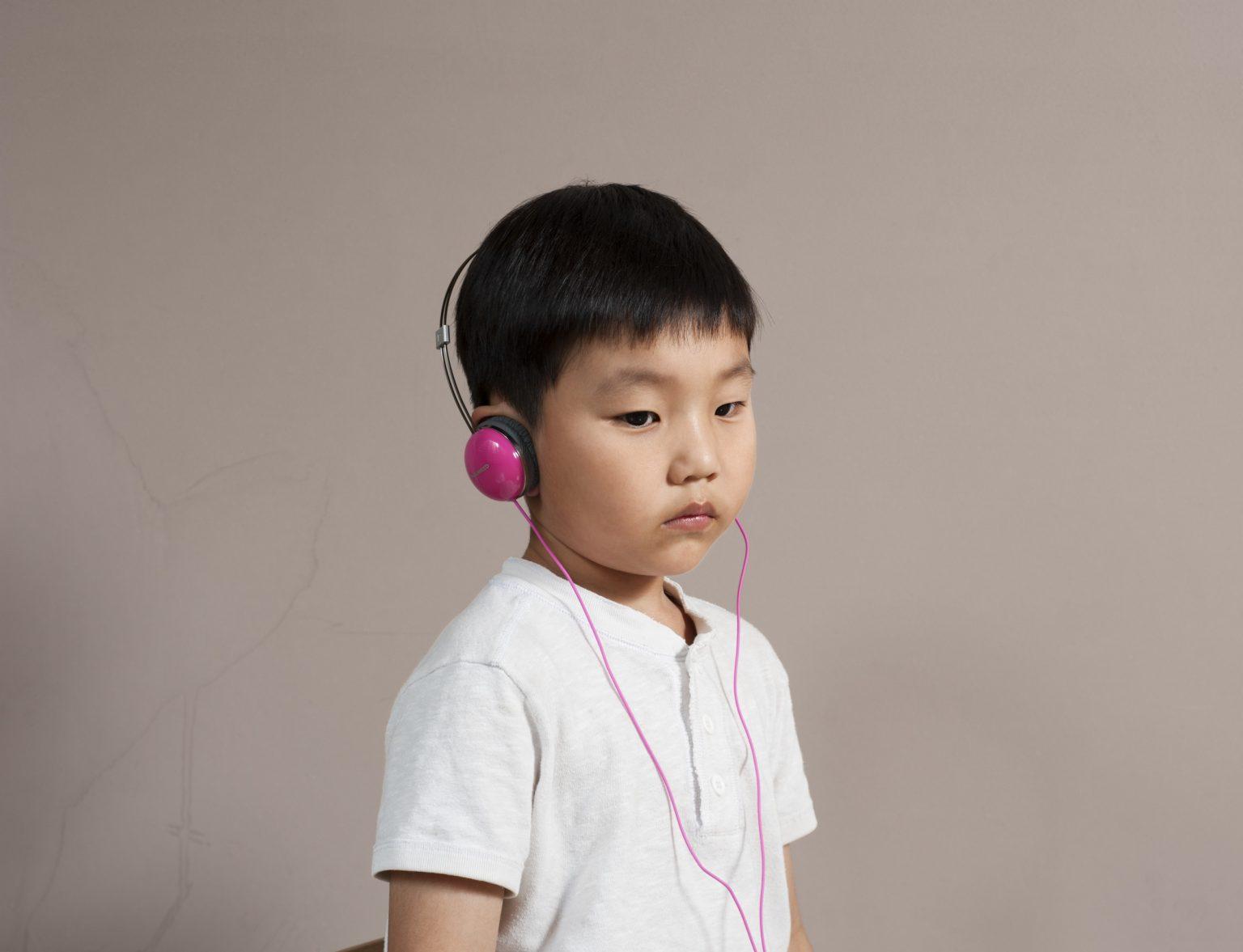 Republic of Korea, Seoul, July 2015: a 3 years old child listening to fairy tales from a tablet in his family apartment./ Repubblica di Corea, Seoul, Luglio 2015: un bambino di 3 anni mentre ascolta delle fiabe da un tablet nel suo appartamento.*Stitched photograph*