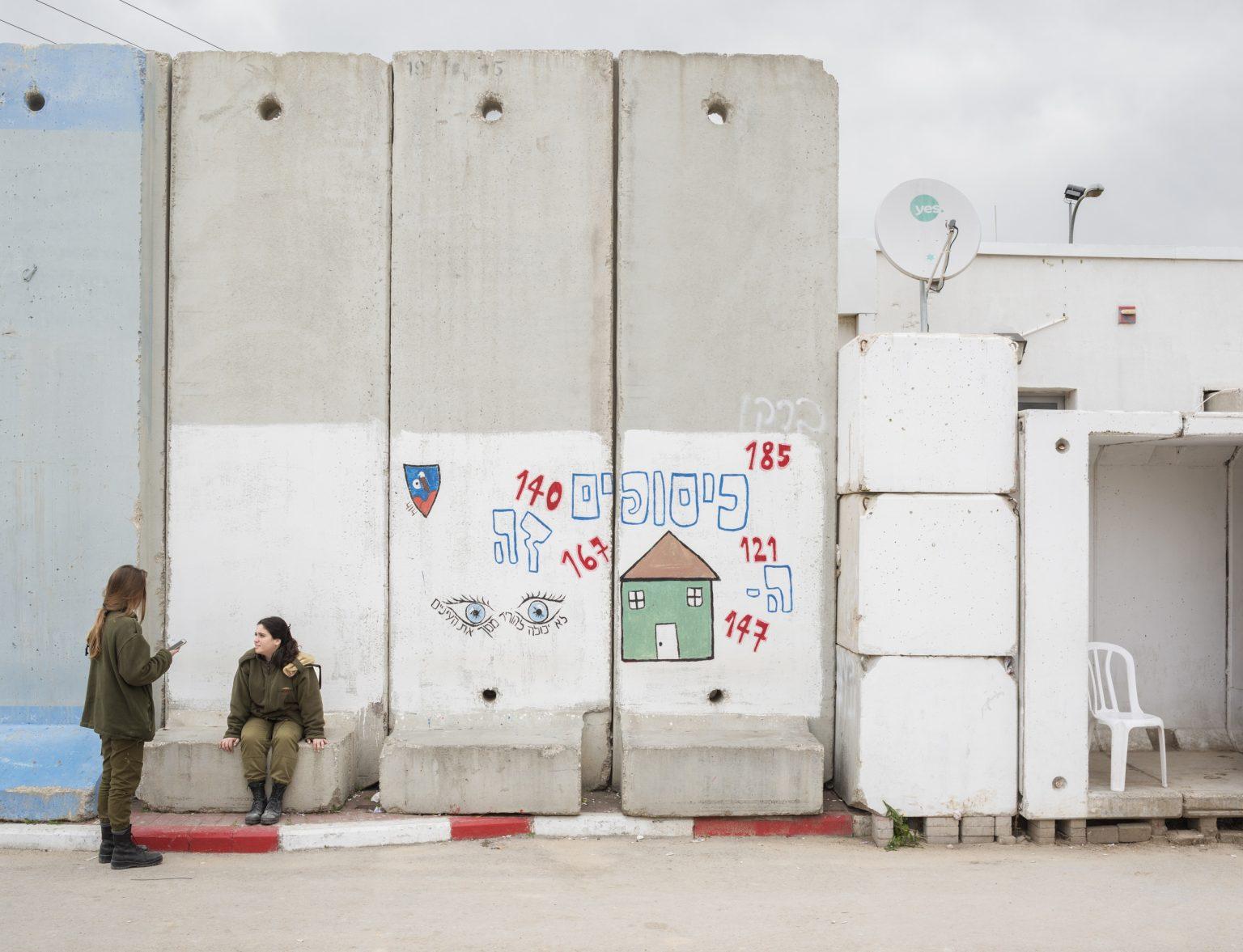 """Kissufim, Israel, February 201?7 - Northwestern Negev Desert.? Operation and Observation Uni?t soldiers at the entrance of ?Kissufim Observation Room, loc?ated in the Kissufim IDF base,? where soldiers can observe th?e opposite side of the border ?via UGV (unmanned ground vehic?le) and cameras placed on Pask?al stations - antennae that ar?e 200-300 meters high. With th?e help of these devices, the u?nit's soldiers can constantly ?control every activity at the ?arab-israelian border. The uni?t belongs to the combat intell?igence corps and it is in char?ge of studying the territory a?nd help the ground forces to u?nderstand the situation on the? ground. For this reason it is? also called """"the eye of the s?tate"""". ><  Kissufim, Israele, ?febbraio 2017 - Deserto nord-o?ccidentale del Negev. Soldates?se della Operation and Observa?tion Unit chiacchierano all'en?trata della Kissufim Observati?on Room, situata nella base de?ll'IDF di Kissufim, dove l'uni?tà di soldati può monitorare i?l lato opposto del confine gra?zie ai dati provenienti dagli ?UGV (unmanned ground vehicle) ?e dalle telecamere posizionate? sulle stazioni Paskal, antenn?e alte 200-300 metri. Con l'ai?uto di queste telecamere l'uni?tà controlla costantemente qua?lsiasi attività presso il conf?ine arabo-israeliano. La Opera?tion and Observation Unit fa p?arte delle unità di combattime?nto e intelligence ed è respon?sabile del controllo delle fro?ntiere, oltre ad essere incari?cata di studiare il territorio? ed aiutare le forze di terra ?a comprendere la situazione su?l campo. Per questo motivo è c?hiamata """"gli occhi dello stato?"""". *Stitched photograph*"""