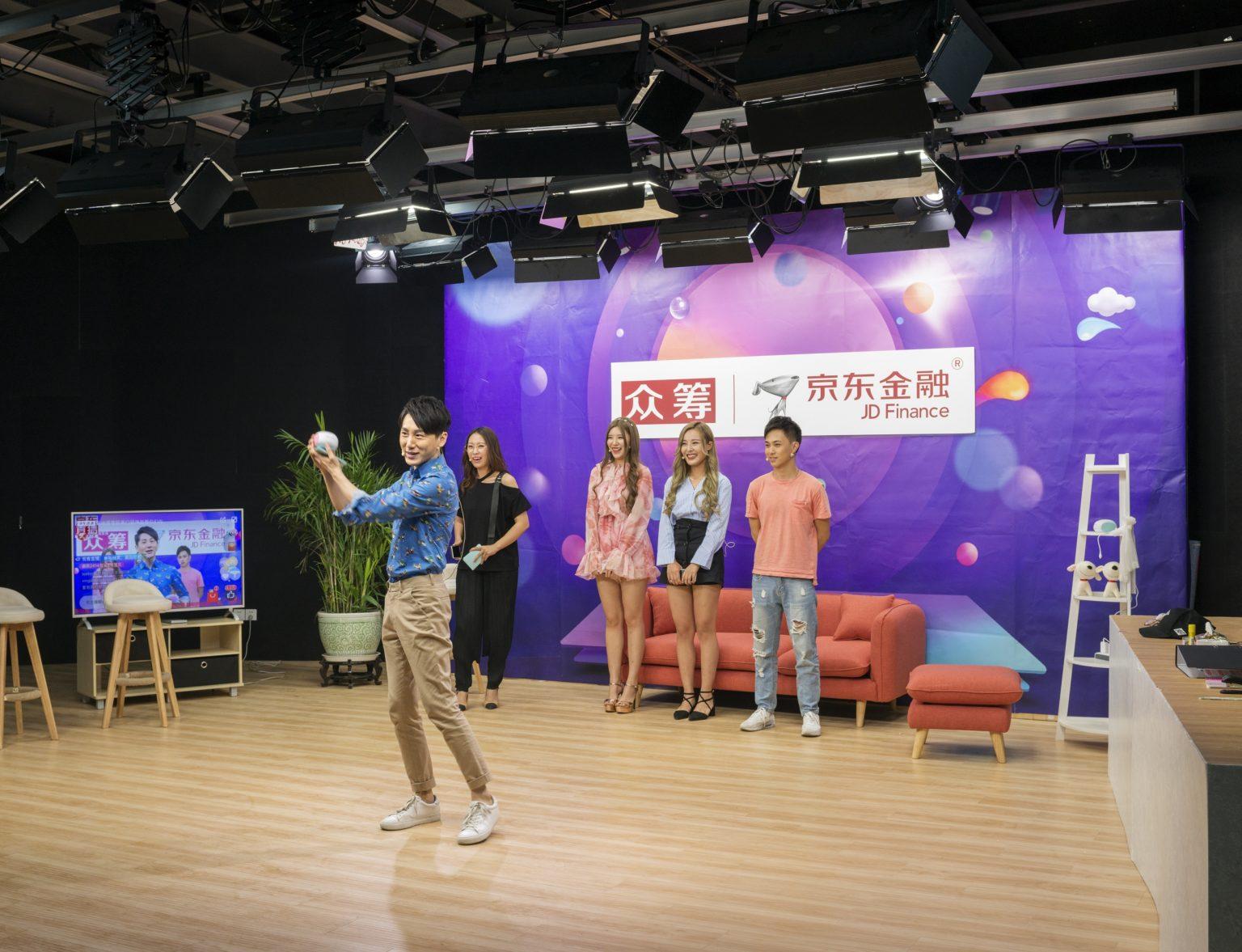 Cina, Pechino, Giugno 2017: Wang Hong (Internet celebrities) durante la trasmissione di un programma promozionale incentrato su prodotti venduti su Alibaba.  Three minutes TV è una agenzia di Wang Hong che rappresenta più di 2000 artisti. L'E-commerce live broadcasting è la sua attività principale, il che significa che i Wang Hong servono come promotori per i prodotti in vendita sulle piattaforme di E-commerce. Offre uno studio con 100 stanze per il live broadcasting per JD.com e 200 stanze per il live broadcasting per Taobao di Alibaba. Il suo volume di vendita nell' e-commerce ha raggiunto i 400.000.000 RMB nel 2016. L'azienda impiega Wang Hong online che lavorano dallo studio o da casa, e I Wang Hong Offline che vivono nei dormitori forniti da Three minutes TV. Tutti I Wang Hong lavorano almeno 6 ore al giorno e hanno 4 giorni liberi al mese. Il loro stipendio base è di 4000 RMB, con commissioni che variano dal 10% all'80%./ China, Beijing, June 2017: Wang Hong (Internet celebrities) broadcasting a promotional show about products sold on Alibaba. Three minutes TV is an Internet celebrities agent company that has more than 2,000 contracted Wang Hong. E-commerce live broadcasting is its main feature, which means the broadcasters serve as promoters for products on E-commerce platforms. It has 100 broadcasting rooms for JD.com and 200 rooms for Alibaba's Taobao. Its E-commerce sales volume in 2016 approached 400,000,000 RMB.  The company uses online broadcasters working from the company's studios and from home and offline broadcasters. The offline ones lives in the dorms provided by three minutes TV. Every kind of Wang Hong works at least 6 hours per day, and has 4 days off per month. Their basic salary is 4000 RMB, with commissions vary from 10% to 80%.