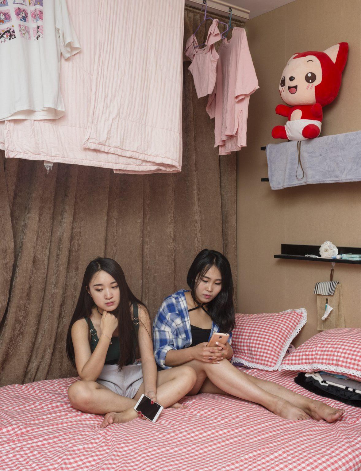 Cina, Pechino, Giugno 2017:  Caicai Yang, di 20 anni e Yufen Xue, di 21 anni, entrambe Wang Hong (Internet celebrites), nei dormitori della Three Minutes Tv dove vivono e lavorano. Caicai Yang ha 10,000 followers and Yufen Xue ha 90,000 followers.  Three minutes TV è una agenzia di Wang Hong che rappresenta più di 2000 artisti. L'E-commerce live broadcasting è la sua attività principale, il che significa che i Wang Hong servono come promotori per i prodotti in vendita sulle piattaforme di E-commerce. Offre uno studio con 100 stanze per il live broadcasting per JD.com e 200 stanze per il live broadcasting per Taobao di Alibaba. Il suo volume di vendita nell' e-commerce ha raggiunto i 400.000.000 RMB nel 2016. L'azienda impiega Wang Hong online che lavorano dallo studio o da casa, e I Wang Hong Offline che vivono nei dormitori forniti da Three minutes TV. Tutti I Wang Hong lavorano almeno 6 ore al giorno e hanno 4 giorni liberi al mese. Il loro stipendio base è di 4000 RMB, con commissioni che variano dal 10% all'80%. / China, Beijing, June 2017: Caicai Yan, 20 years old, and Yufen Xue, 21 years old, both Wang Hong (Internet celebrities) in the dormitories of Three Minutes Tv where they live and work. Caicai Yang has 10,000 followers and Yufen Xue has 90,000 followers.Three minutes TV is an Internet celebrities agent company that has more than 2,000 contracted Wang Hong. E-commerce live broadcasting is its main feature, which means the broadcasters serve as promoters for products on E-commerce platforms. It has 100 broadcasting rooms for JD.com and 200 rooms for Alibaba's Taobao. Its E-commerce sales volume in 2016 approached 400,000,000 RMB.  The company uses online broadcasters working from the company's studios and from home and offline broadcasters. The offline ones lives in the dorms provided by three minutes TV. Every kind of Wang Hong works at least 6 hours per day, and has 4 days off per month. Their basic salary is 4000 RMB, with commissions va