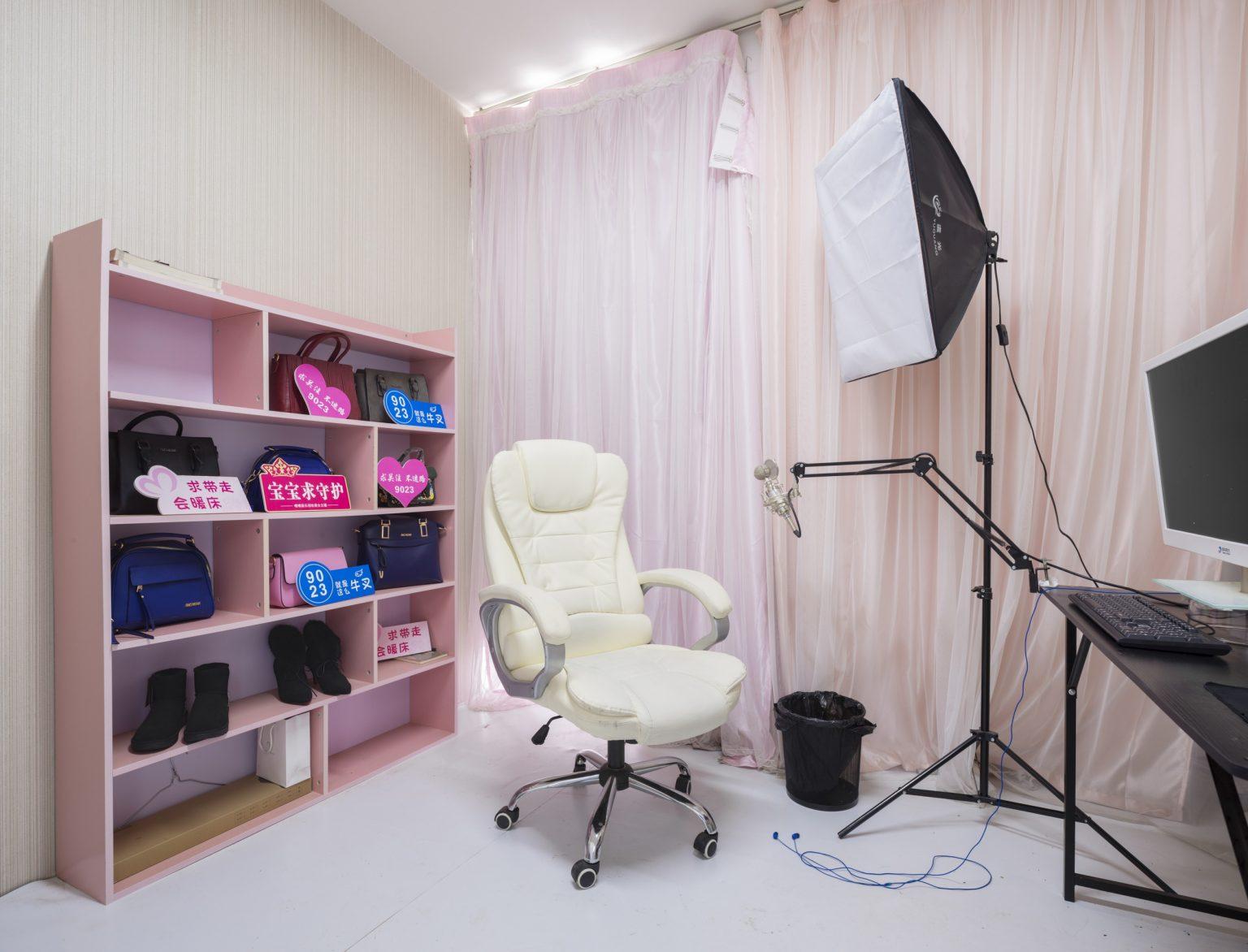 Cina, Pechino, Giugno 2017: una stanza per il live streaming promozionale di prodotti in vendita su Alibaba nello studio della Three Minutes TV. Three minutes TV è una agenzia di Wang Hong che rappresenta più di 2000 artisti. L'E-commerce live broadcasting è la sua attività principale, il che significa che i Wang Hong servono come promotori per i prodotti in vendita sulle piattaforme di E-commerce. Offre uno studio con 100 stanze per il live broadcasting per JD.com e 200 stanze per il live broadcasting per Taobao di Alibaba. Il suo volume di vendita nell' e-commerce ha raggiunto i 400.000.000 RMB nel 2016. L'azienda impiega Wang Hong online che lavorano dallo studio o da casa, e I Wang Hong Offline che vivono nei dormitori forniti da Three minutes TV. Tutti I Wang Hong lavorano almeno 6 ore al giorno e hanno 4 giorni liberi al mese. Il loro stipendio base è di 4000 RMB, con commissioni che variano dal 10% all'80%./ China, Beijing, June 2017: a room for the live broadcasting promotions of products sold on Alibaba.  Three minutes TV is an Internet celebrities agent company that has more than 2,000 contracted Wang Hong. E-commerce live broadcasting is its main feature, which means the broadcasters serve as promoters for products on E-commerce platforms. It has 100 broadcasting rooms for JD.com and 200 rooms for Alibaba's Taobao. Its E-commerce sales volume in 2016 approached 400,000,000 RMB.  The company uses online broadcasters working from the company's studios and from home and offline broadcasters. The offline ones lives in the dorms provided by three minutes TV. Every kind of Wang Hong works at least 6 hours per day, and has 4 days off per month. Their basic salary is 4000 RMB, with commissions vary from 10% to 80%.*Stitched photograph*