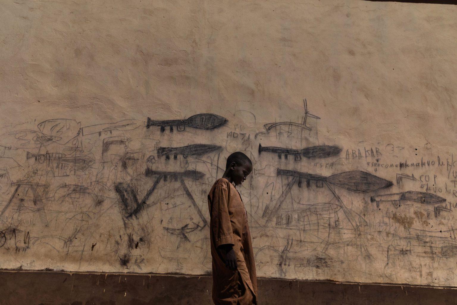 """Africa, Chad, Melea, October 2018 - Orphaned children, mainly Nigerian refugees, live together as a group in the Koran schools. During the day, they go begging and are known as Almajiri. These children, who live in the Lake Chad basin, are growing up in a constant situation of war. All they?ve ever known are weapons and deaths, which they draw on the walls of the city. Almajiri derives from an Arabic word """"Al-Muhajirun"""", meaning """"person who leaves his home in search of Islamic knowledge"""".>< Africa, Ciad, Melea, Ottobre 2018 - Bambini orfani, soprattutto rifugiati nigeriani, vivono insieme come gruppo nelle scuole di Corano. Durante il giorno chiedono l'elemosina e sono conosciuti come Almajiri. Questi bambini, che vivono nel bacino del Lago Ciad, stanno crescendo in una situazione di conflitto perenne e  conoscono solamente armi e morti, che disegnano sui muri della città. Almajiri deriva da una parola Araba  """"Al-Muhajirun"""", che significa """"persona che lascia la sua casa in cerca di conoscenza dell'Islam"""".*** SPECIAL   FEE   APPLIES *** *** Local Caption *** 01362916"""
