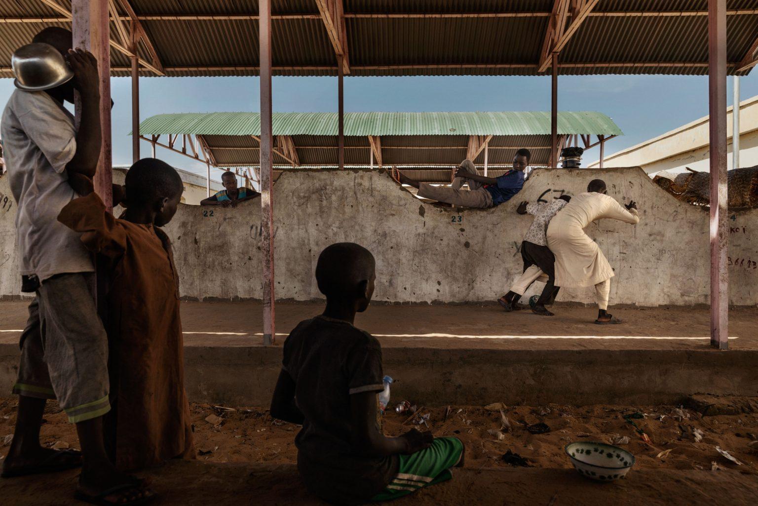 """Africa, Chad, Bol, October 2018 - Some kids play football with a makeshift ball. Orphaned children, mainly Nigerian refugees, live together as a group in the Koran schools. During the day, they go begging and are known as Almajiri. Almajiri comes from an Arabic word """"Al-Muhajirun"""" which means """"a person who leaves his home in search of Islamic knowledge"""". >< Africa, Ciad, Bol, Ottobre 2018 - Alcuni bambini giocano a calcio con una palla improvvisata. Bambini orfani, principalmente rifugiati nigeriani, vivono insieme come gruppo nelle scuole del Corano. Durante il giorno mendicano e sono conosciuti come Almajiri. Almajiri viene dalla parola Araba """"Al-Muhajirun"""", che  significa """"persona che lascia la sua casa in cerca di conoscenza dell'Islam. *** SPECIAL   FEE   APPLIES *** *** Local Caption *** 01362914"""