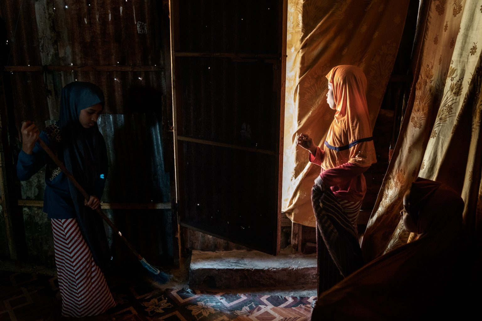"""Africa, Somalia, Benaadir region. Mogadishu. Hassan's daughters are seen at home doing housework. Hassan Ali Sufi, 49 years old. In 1981, he started working as an assistant chef in """"Casa Italia"""". A few years, later he became a chef. He left Somalia in 1991, and went to Yemen. In 1994 he went back to Somalia and then left again for Yemen, where he stayed until 2015, then came back to Somalia again because of the war. He used to have a good salary, but now he is struggling every day to survive. He pays 40 USD per month for the rent of his house. He has ten children, 7 boys, and 3 girls.  Since 2015, when he came back to Somalia, he has experienced 2 bomb attacks, but luckily, he was not injured. Hassan's daughters are seen at home doing the housework."""