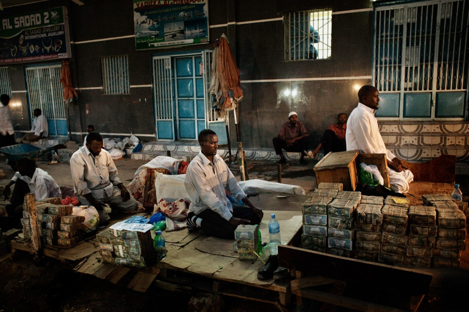 A currency exchangers pray at the central market in Hargeisa during the evening prayer. Inflation in Somalia is very high. The US Dollars - Somali Shilling currency exchange rate is 1 = 580.400. The bills are worth almost nothing. For 100USD you receive a full plastic bag of shillings.
