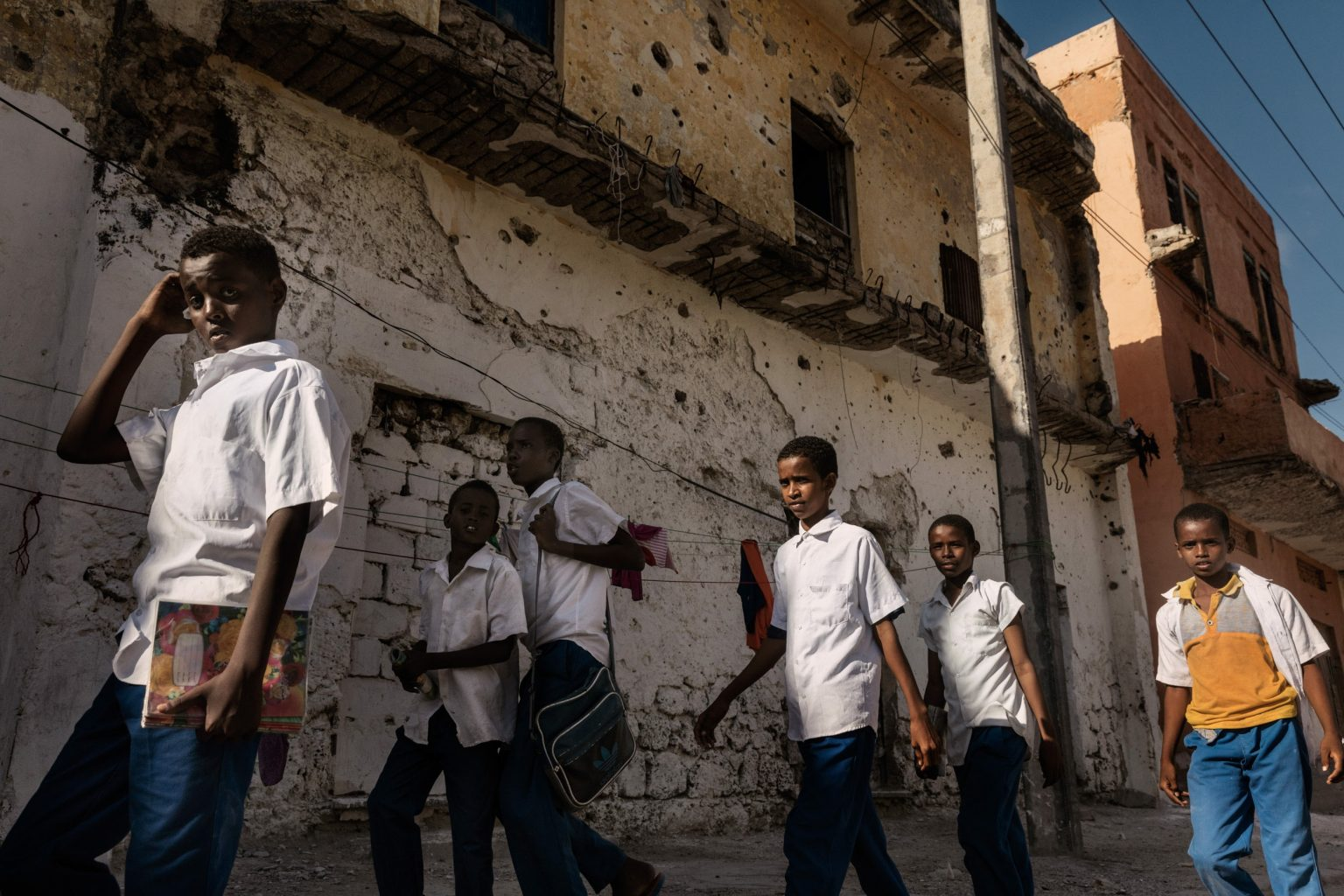 """Africa, Somalia, Benaadir region. Mogadishu. 19/ 09/2017 Students return home after school, walking through the war-torn Hamarweyne and Shangani districts, located in the old town of the Somali capital; the literal meaning of Hamarweyne is """"big city"""" or """"old town"""". The climate of terror, the corrupt state administration and the formation of armed clan groups are all contributing factors to the disease that has been devouring Somalia for decades, but rising up against it today is the collective sentiment of a people that does not wish to feel alone and has decided to take its destiny into its own hands in order to conquer fear and look to the future."""
