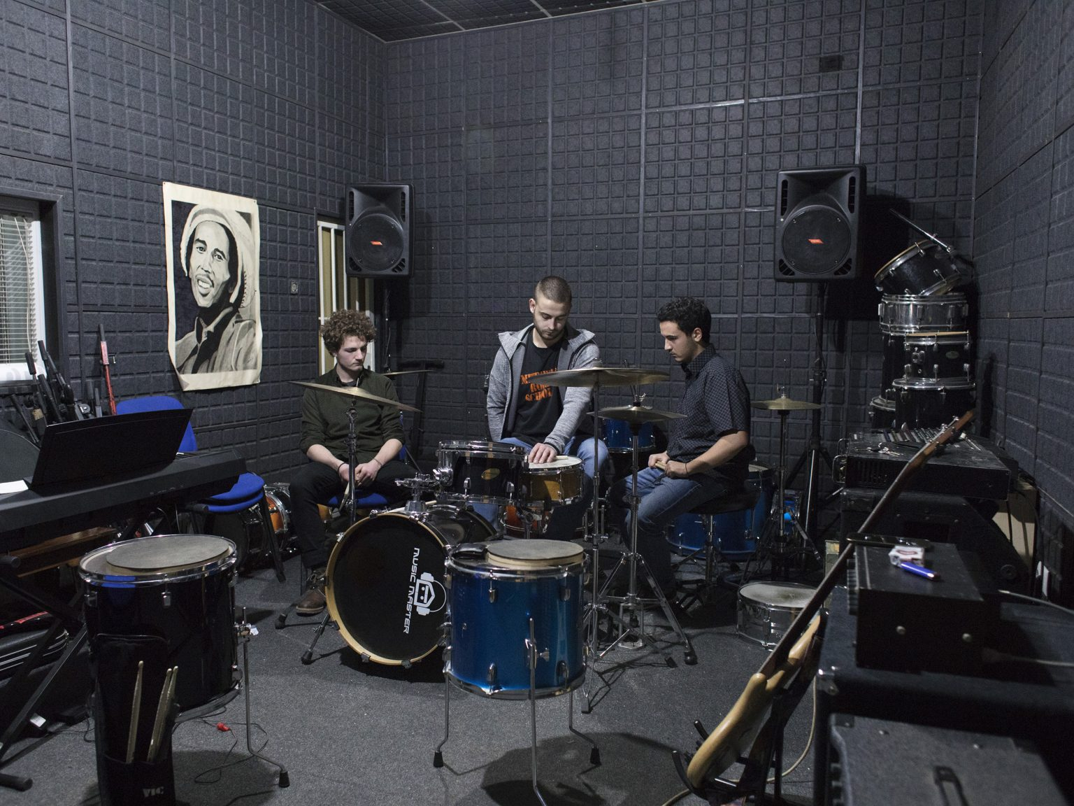 """Filip (center), drum teacher from Northern Mitrovicë / Kosovska Mitrovica and Dardan and Aron, students from South Mitrovicë / Kosovska Mitrovica, practicing at Mitrovica Rock school. The school started in 2008 with a summer school in Skopje by """"Musicians Without Borders"""" and CBM. In 2011, the school became an NGO and the first mixed band, called """"The ArTchitects"""", with both Serbian and Albanian musicians, was created. Today the are 7 active mixed bands."""
