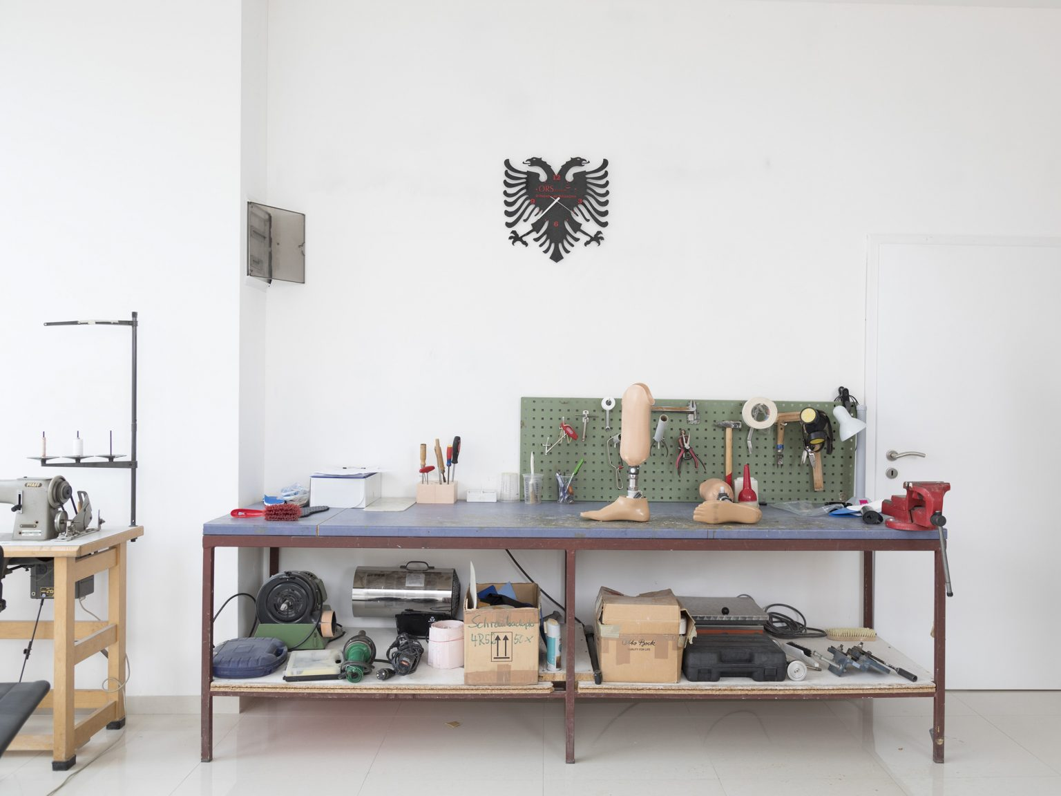 A working bench inside ORS, a company which manufactures prosthetic limbs and provides physiotherapy for invalids, most of which have lost limbs on landmines. There is no exact data regarding the number of land-mines victims in the country. According to ORS there are about 100 former UCK soldier and about 200 civilians, while many other have left the country to seek better cures. However according to the UN, there are about 10 civil invalids for each war invalid. In 2015 ORS provided free prosthetic limbs for about 40 civilians. Their cost is very high - from 2000 euros to 6000 euros - and the pension given by the government to civil invalids is about 70 euros/month.