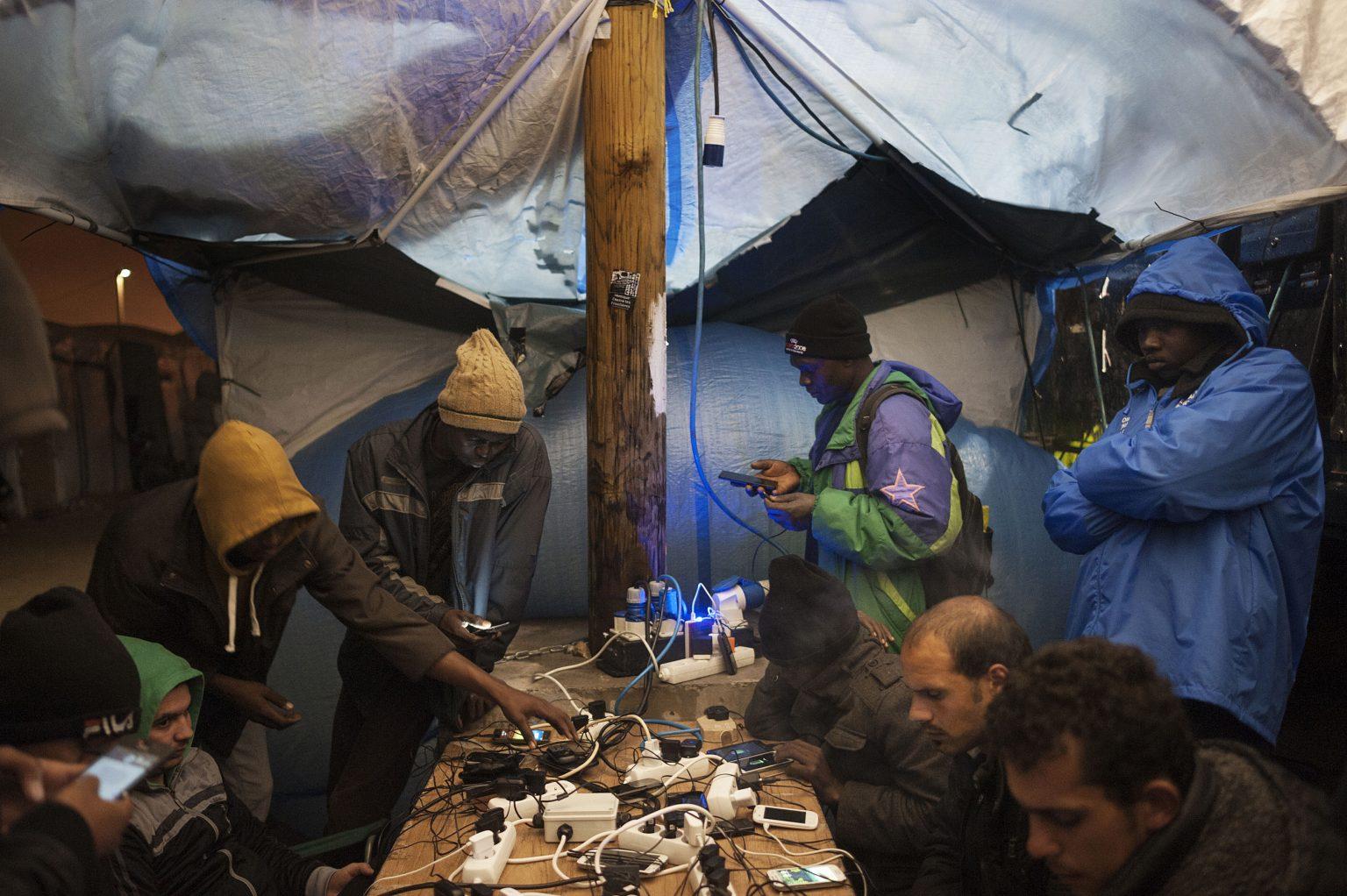 Calais, France, November 6th 2015 - Migrants charging their phones on sockets plugged into a generator at a camp.   ><  Calais, Francia, 6 novembre 2015 - Immigrati caricano i telefoni a una presa collegata a un generatore del campo profughi. *** Local Caption *** 00566955