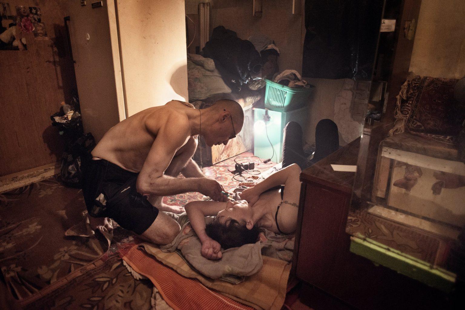 Yekaterinburg, Russia, November 2013 - Andrey injects a dose of krokodil to Zhanna in his apartment in the Uralmash district. >< Yekaterinburg, Russia, novembre 2013 - Andrey inietta una dose di Krokodil a Zhanna nel suo appartamento nel quartiere di Uralmash.