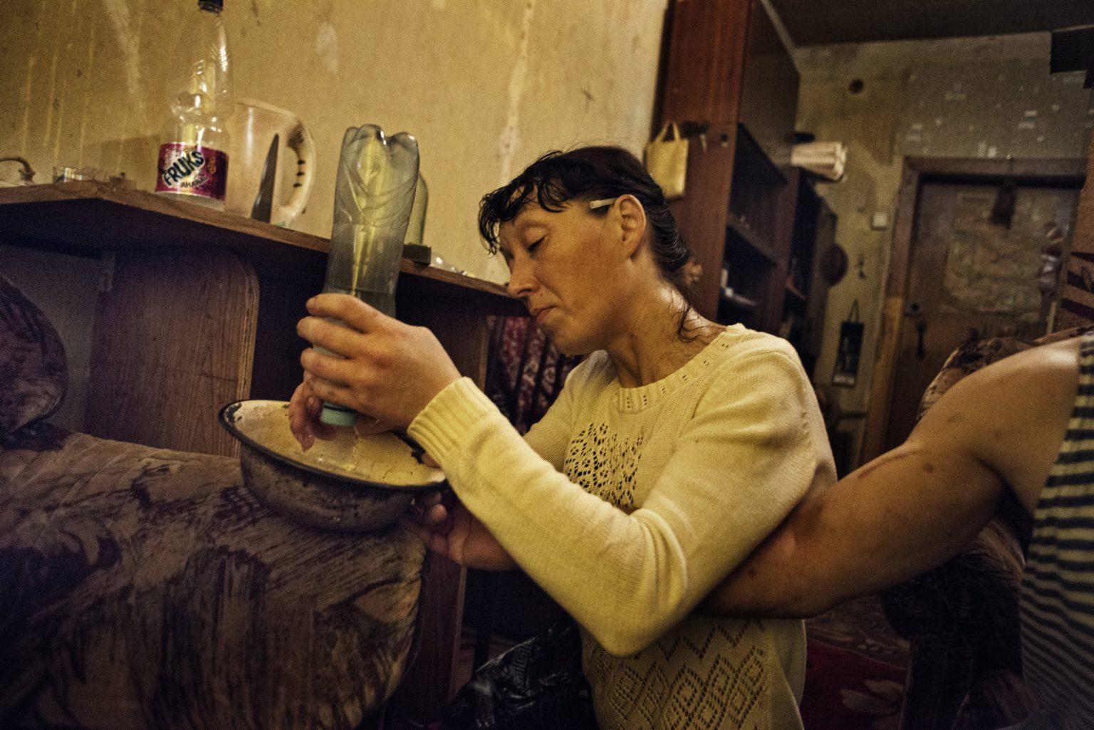 Yekaterinburg, Russia, November 2013 - Zhanna under the effect of Krokodil, trying to filter water from a bottle. (She died in 2015 due to the long use of Krokodil). >< Yekaterinburg, Russia, novembre 2013 - Sotto l'effetto della Krokodil Zhanna prova a filtrare dell'acqua da una bottiglia. (Zhanna è morta nel 2015 a seguito dell'uso prolungato di Krokdoil).