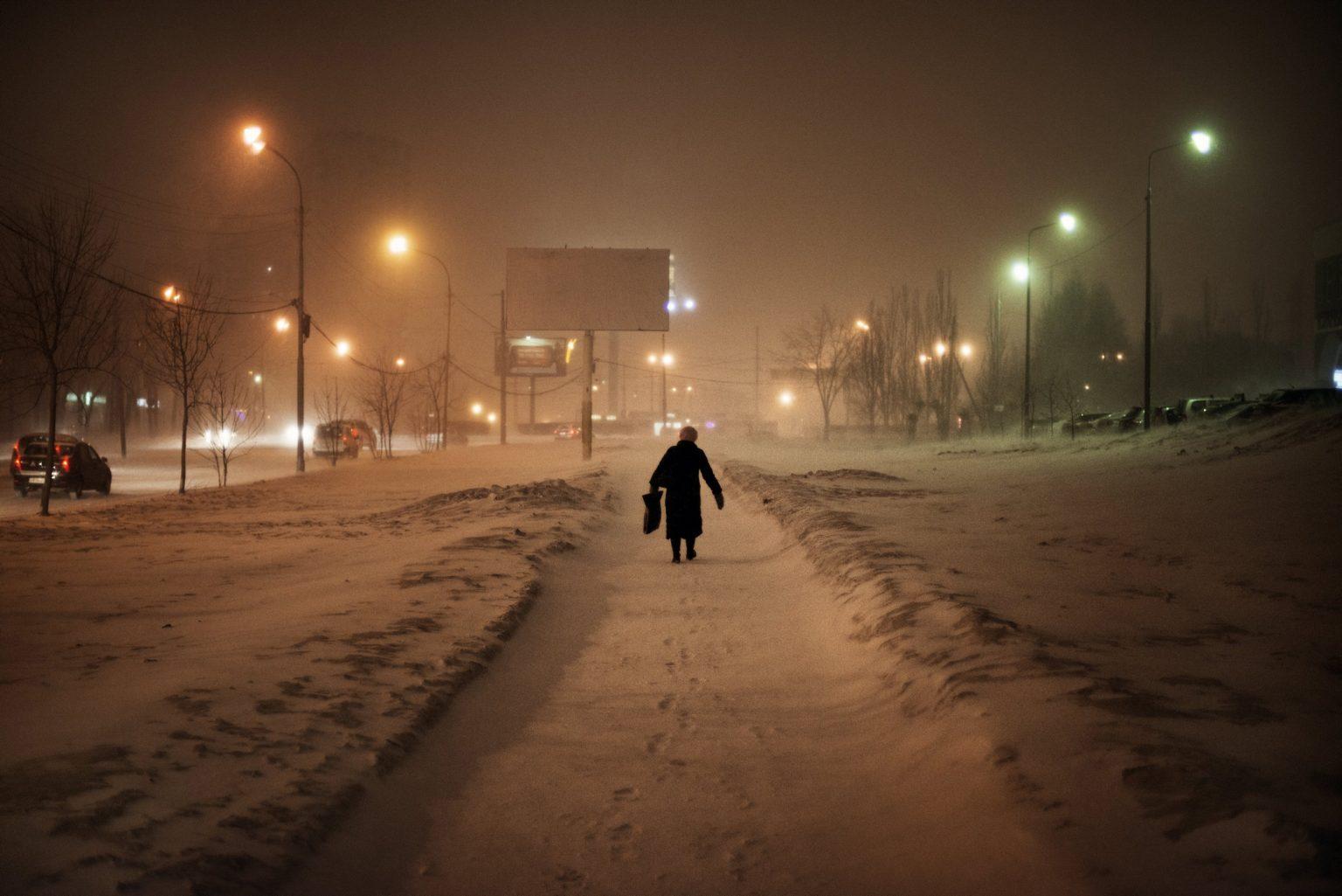Yekaterinburg, Russia, March 2013 - A woman walks on a street in the outskirts of Yekaterinburg. >< Yekaterinburg, Russia, marzo 2013 - Una donna cammina lungo una strada nella periferia di Yekaterinburg.