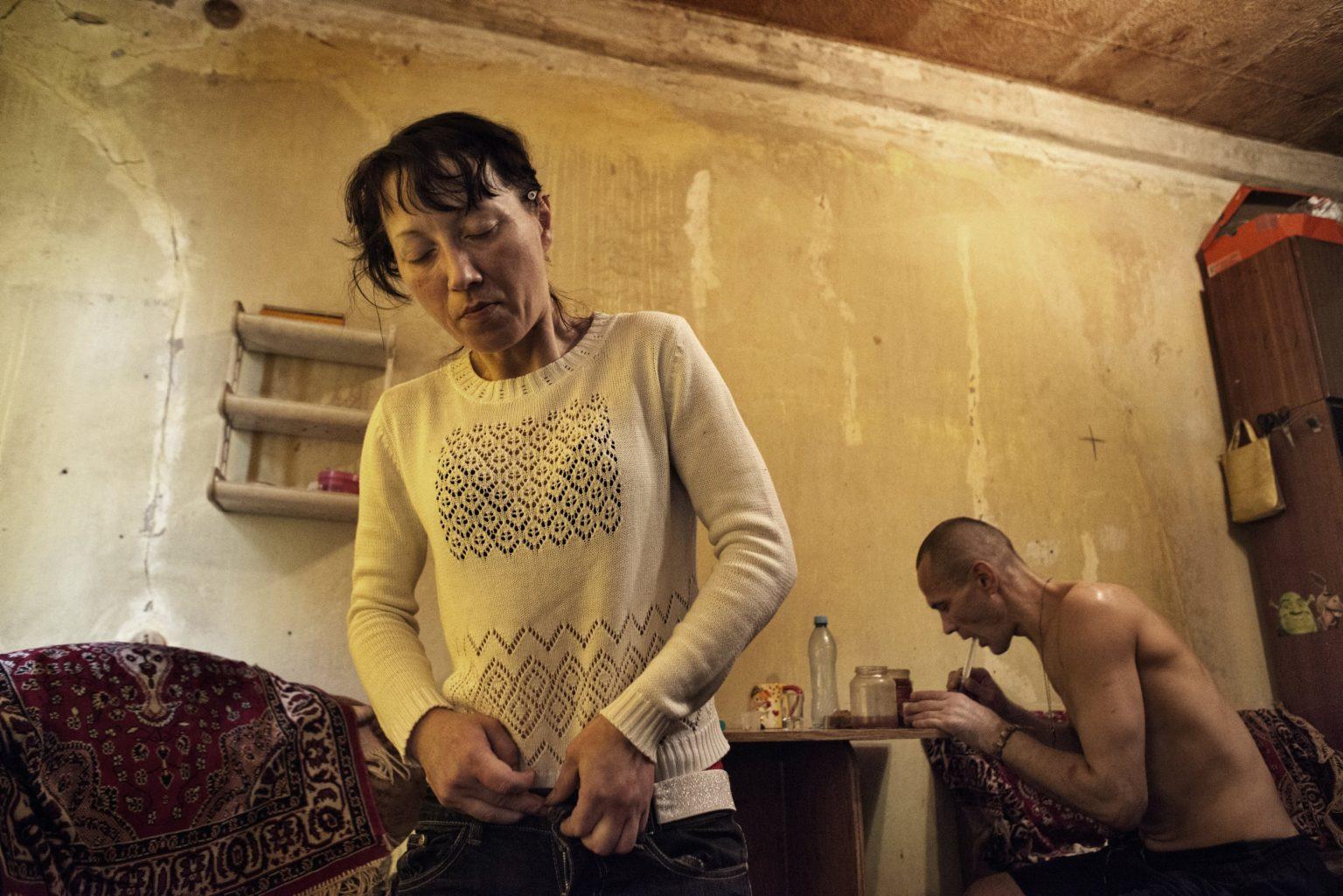 Yekaterinburg, Russia, November 2013 - Zhanna under the influence of drugs, while Andrey draws water from a pot to get sulfur. >< Yekaterinburg, Russia, novembre 2013 - Zhanna in piedi dopo aver assunto la Krokodil, mentre Andrey toglie l'acqua da una pentola per estrarne lo zolfo.