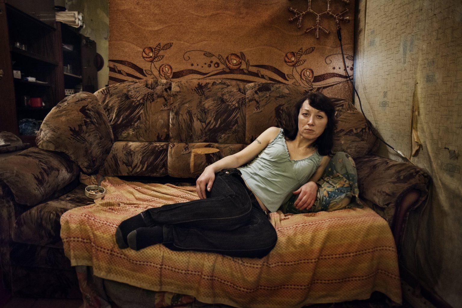 Yekaterinburg, Russia, November 2013 - Zhanna under the effect of Krokodil, lying on a couch in an apartment in the district of Uralmash. (She died in 2015 due to the long use of Krokodil). >< Yekaterinburg, Russia, novembre 2013 - Zhanna sotto l'effetto della Krokodil siede su un divano in un appartamento nel quartiere di Uralmash. (Zhanna è morta nel 2015 a seguito dell'uso prolungato di Krokdoil).