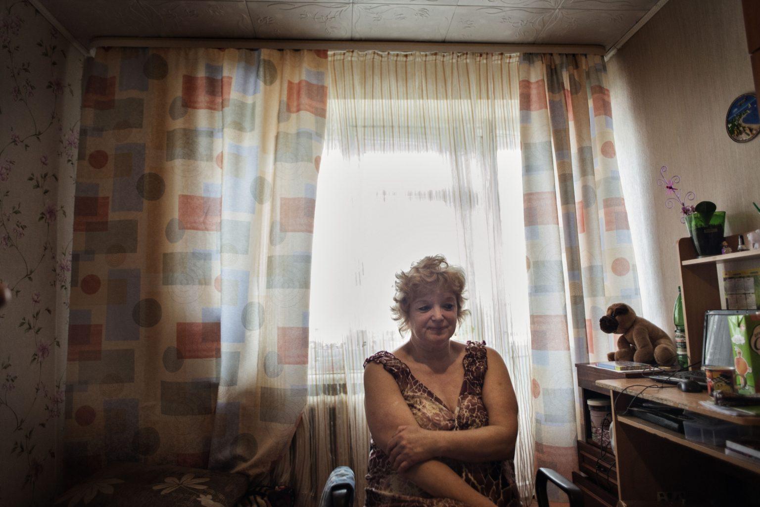 Yekaterinburg, Russia, March 2016 - Lyudmila in her flat in Uralmash district. Her daughter Zhanna died in 2015 due to the long use of Krokodil. Lyudmila is now living with her granddaughter. >< Yekaterinburg, Russia, Marzo 2016 - Lyudmila siede nel suo appartamento nel quartiere di Uralmash. Sua figlia Zhanna è morta nel 2015 a causa di un uso prolungato di Krokodil. Lyudmila vive con sua nipote.