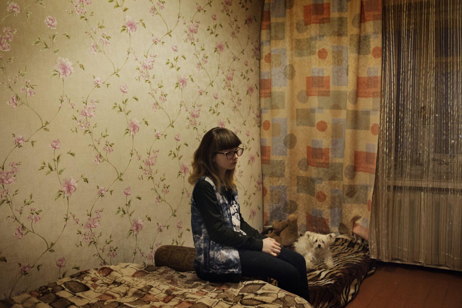 Yekaterinburg, Russia, March 2016 - Diana in the flat where she's living with her grandmother. Her mother Olga died in 2015 due to the long use of Krokodil. >< Yekaterinburg, Russia, marzo 2016 - Diana siede nell'appartamento dove vive con la nonna. Sua madre Zhanna è morta nel 2015 a causa di un uso prolungato di Krokodil.