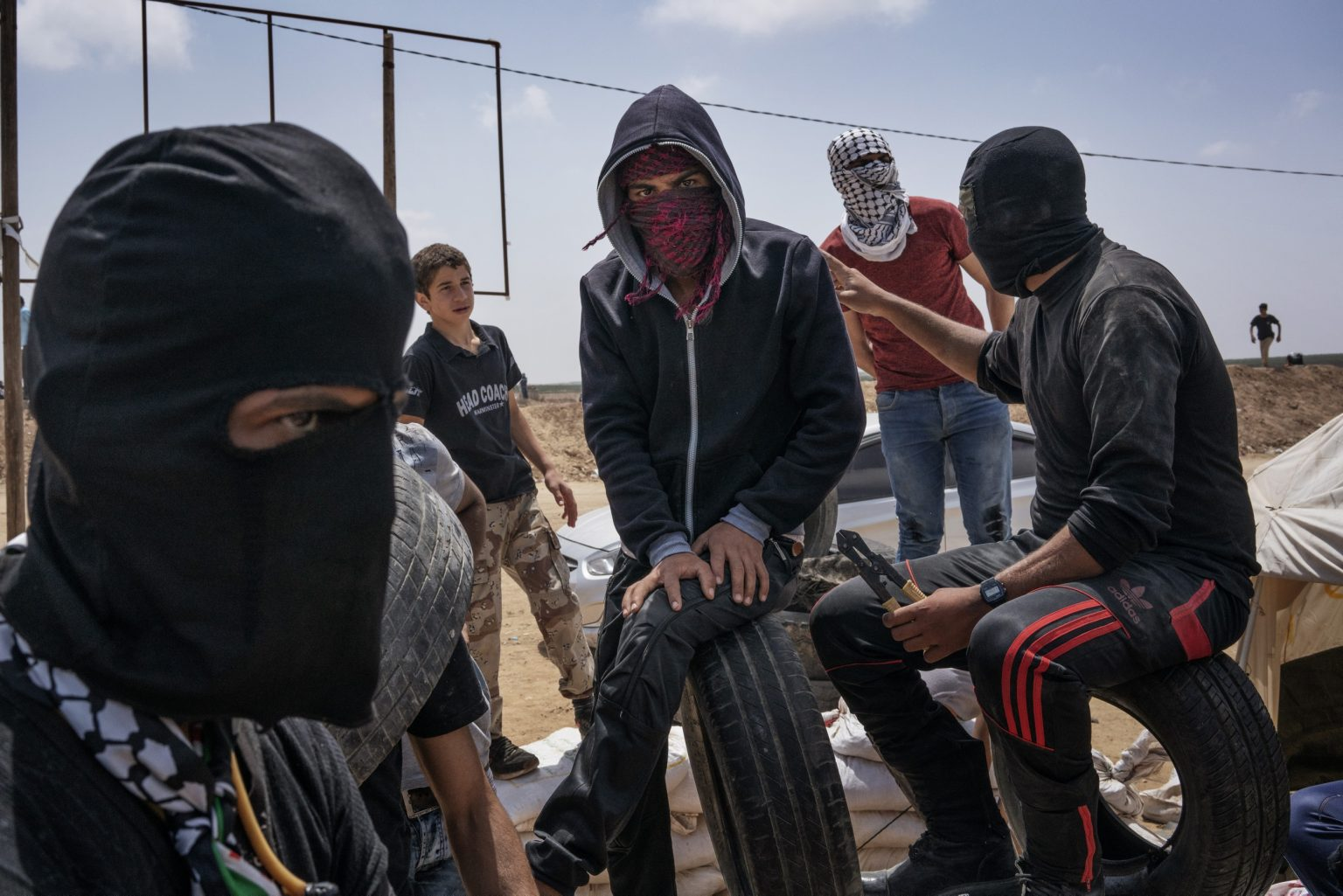 Gaza Strip, May 2018 - A group of young Palestinian protesters sit on top of tires along the Israel-Gaza border. >< Striscia di Gaza, maggio 2018 - Un gruppo di ragazzi palestinesi siede sopra dei copertoni lungo il confine tra Gaza e Israele.