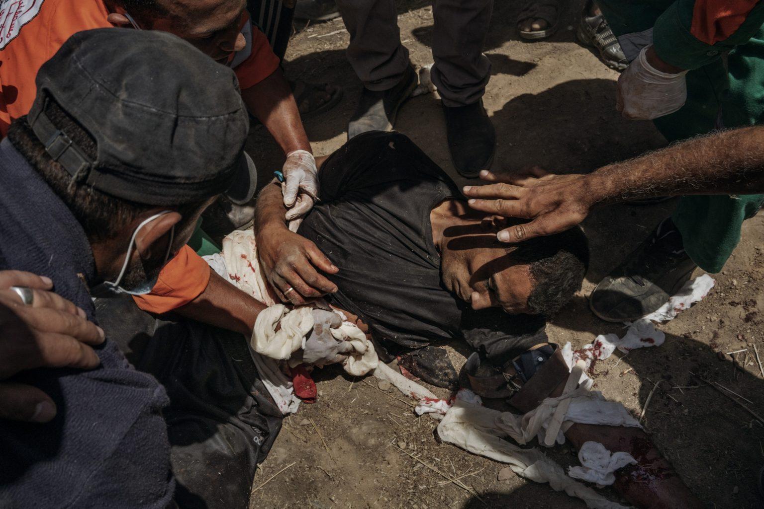 Gaza Strip, May 2018 - Paramedics assist a man who was injured in the chest and arms by Israeli troops along the Gaza border. >< Striscia di Gaza, maggio 2018 - Paramedici assistono un uomo palestinese ferito al petto da una pallottola durante le proteste lungo il confine tra Gaza e Israele.