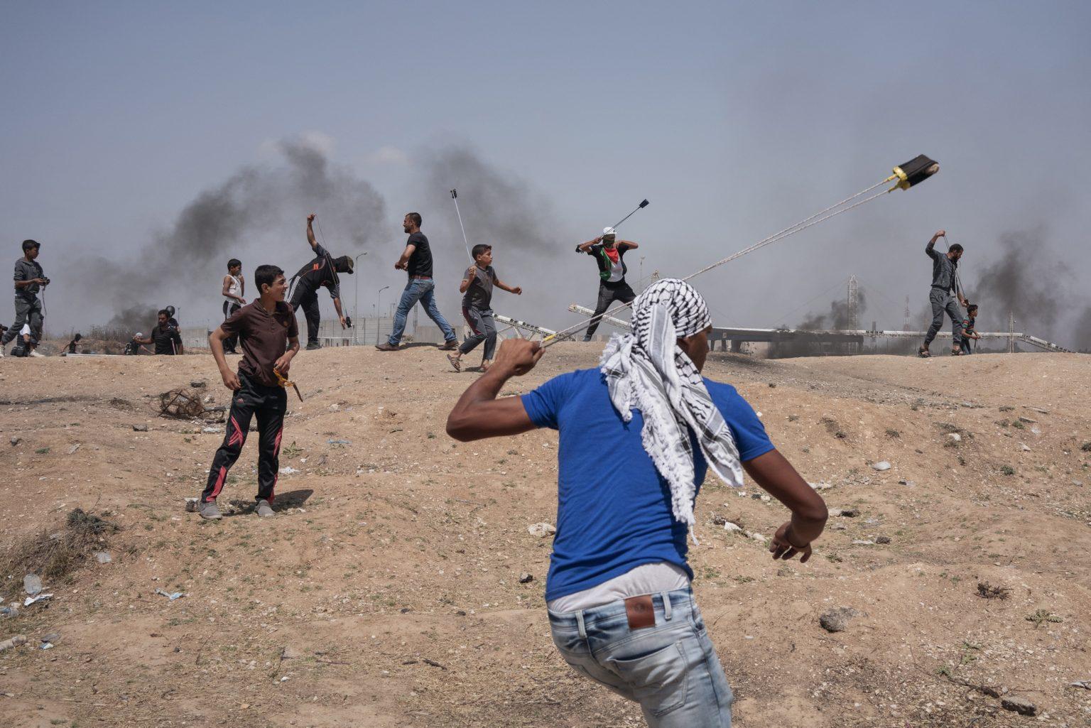 Gaza Strip, May 2018 - Palestinian protesters use slingshots to throw stones near the border fence with Israel during the demonstration. >< Striscia di Gaza, maggio 2018 - Dimostranti palestinesi usano delle fionde per lanciare sassi verso il confine israeliano.