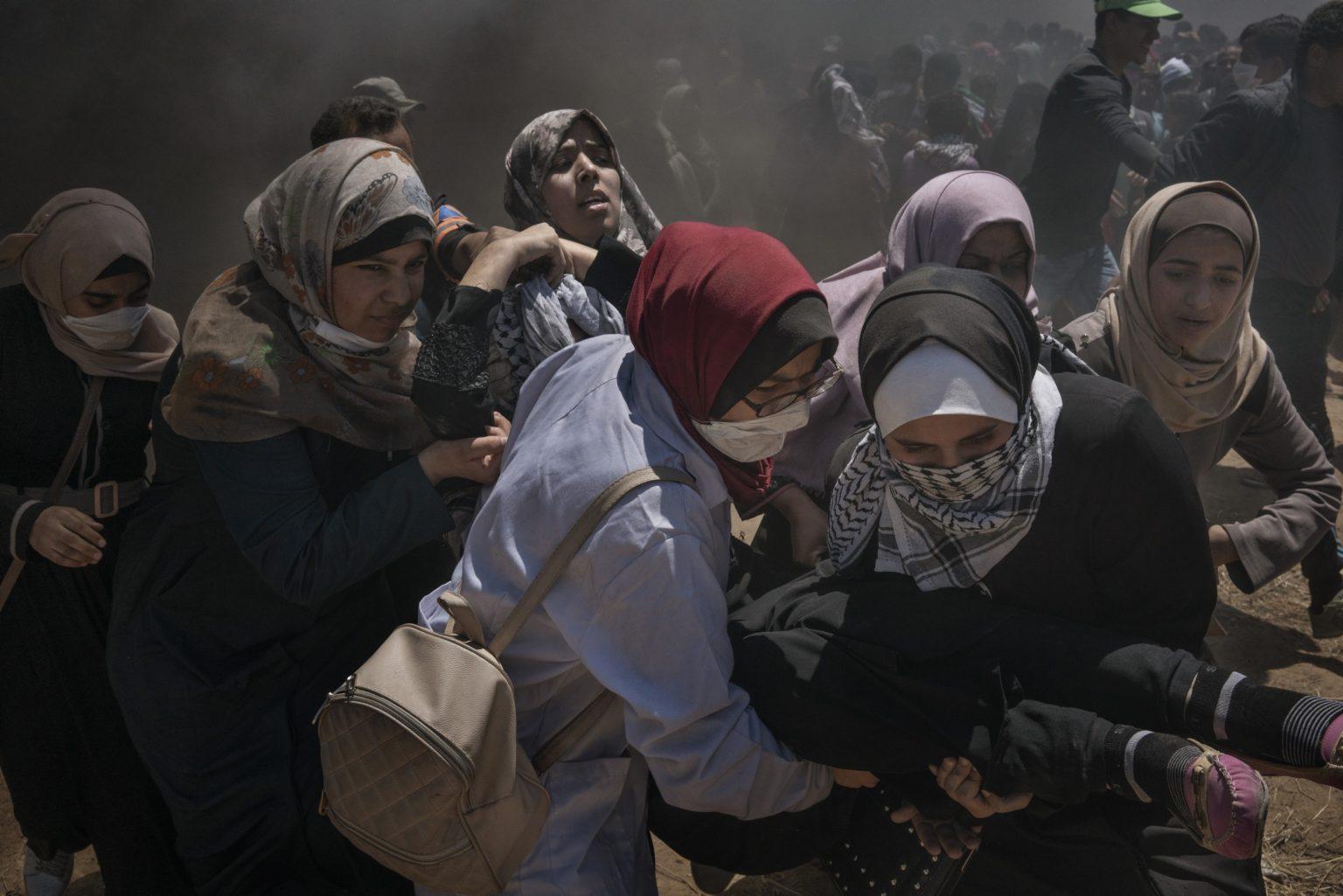 Gaza Strip, May 2018 - A wounded woman is evacuated by other women after she was injured in the head during the protest along the Gaza-Israel border. >< Striscia di Gaza, maggio 2018 - Una donna colpita alla testa da una pallottola viene trasportata via durante le proteste lungo il confine tra Gaza e Israele.