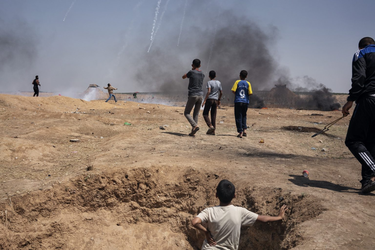 Gaza Strip, May 2018 - A Palestinian boy takes shelter while Israely soldiers fired tear gas.><  Striscia di Gaza, maggio 2018 - Un ragazzo palestinese trova riparo dentro una buca mentre soldati palestinesi lanciano gas lacrimogeni.