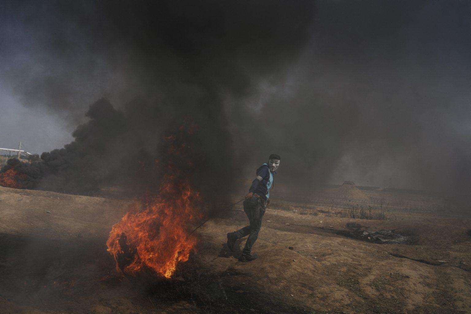 Gaza Strip, May 2018 - A Palestinian demonstrator moves a burning tire along the Gaza-Israel border. >< Striscia di Gaza, maggio 2018 - Un manifestante palestinese trascina un copertone in fiamme verso il confine israeliano.
