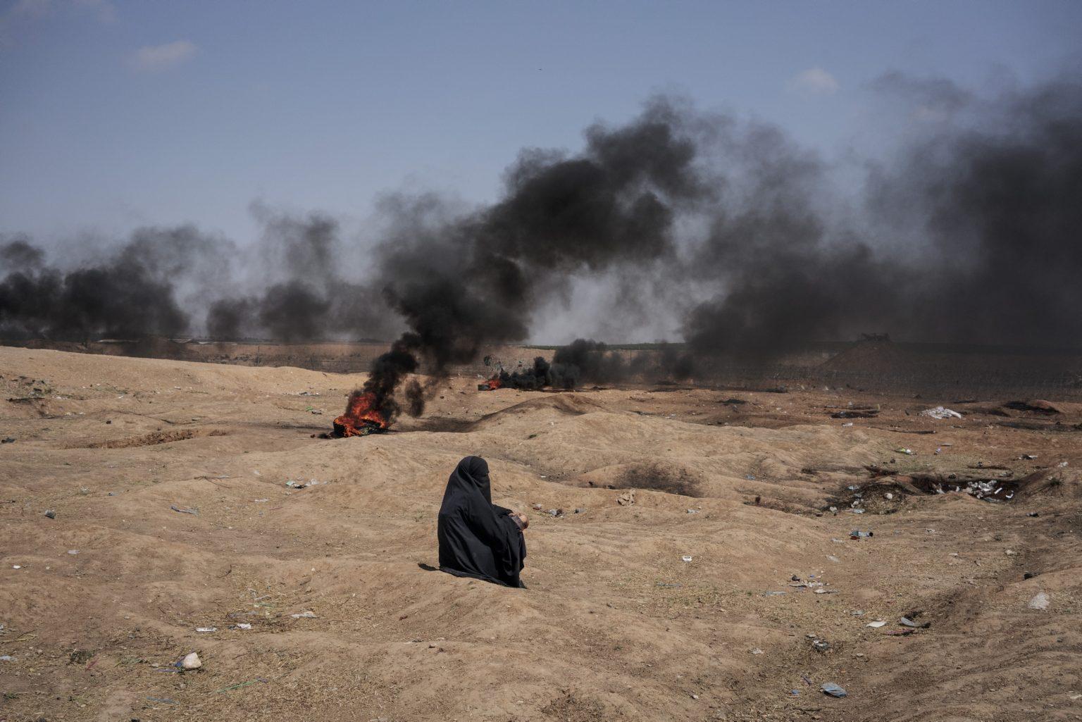 Gaza Strip, May 2018 - A woman seats near the border between Gaza and Israel during the protest. >< Striscia di Gaza, maggio 2018 - Una donna siede vicino al confine tra Gaza e Israele durante le proteste