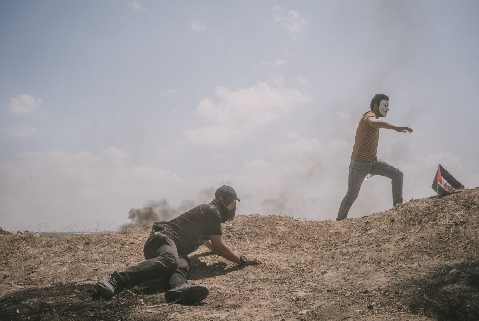 Gaza Strip, May 2018 - A man hides behind an embankment during the protest along the Gaza-Israel border. >< Striscia di Gaza, maggio 2018 - Un uomo si ripara durante le proteste lungo il confine tra Gaza e Israele.