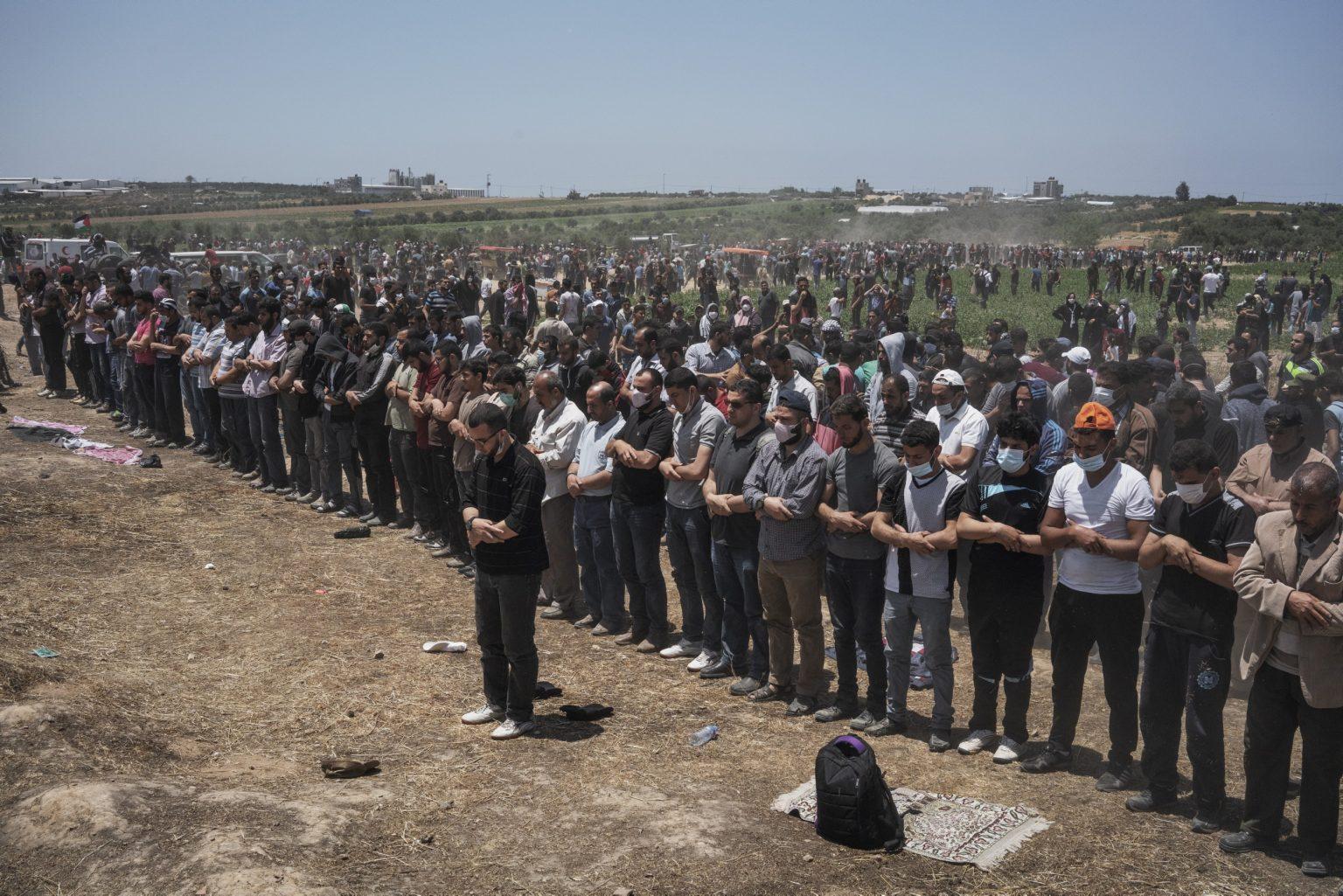 Gaza Strip, May 2018 - Palestinian men pray during the protest along the Gaza-Israel border. >< Striscia di Gaza,maggio 2018 - Palestinesi pregano durante le proteste lungo il confine tra Gaza e Israele.