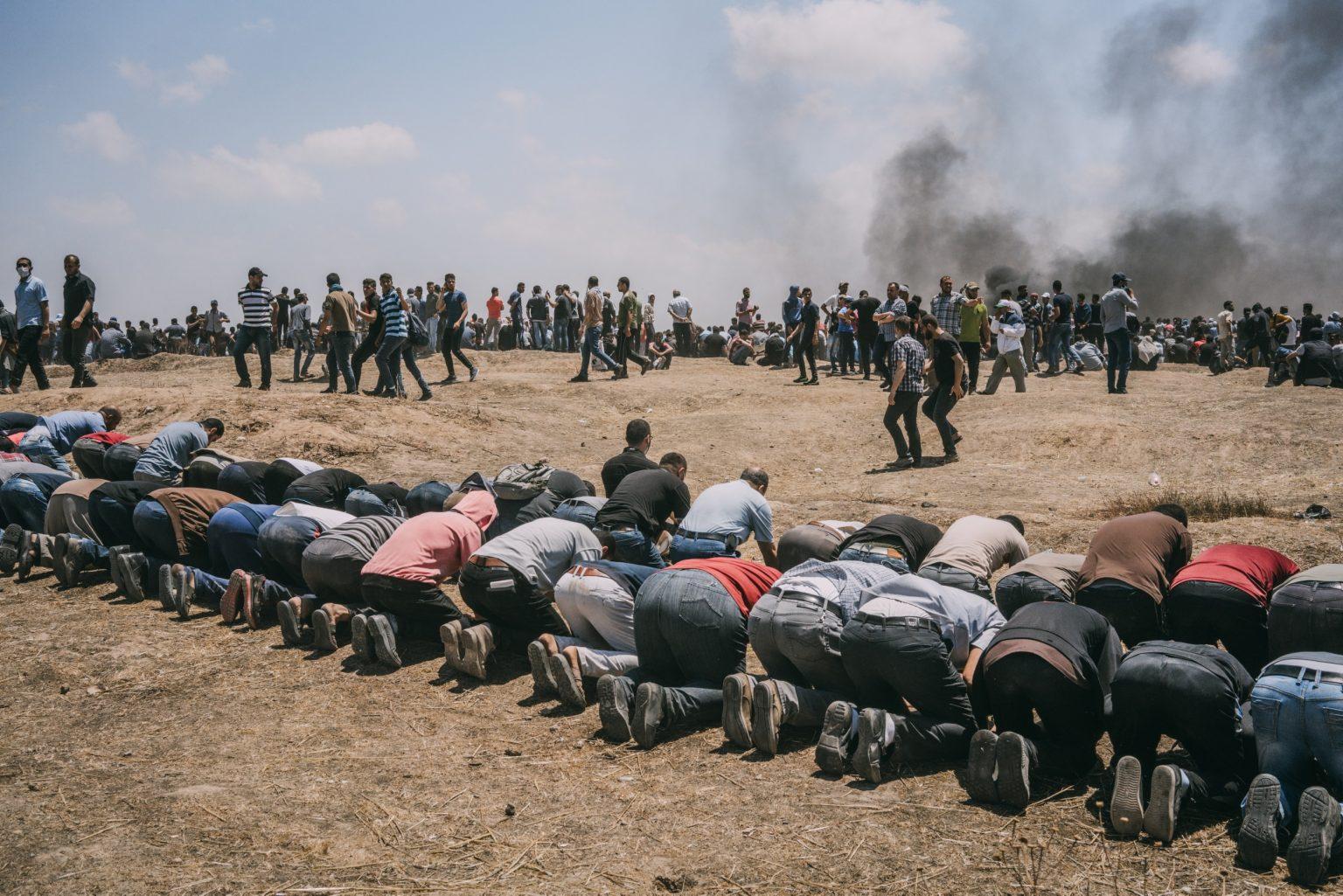 Gaza Strip, May 2018 - Palestinian men pray during the protest along the Gaza-Israel border. >< Striscia di Gaza, maggio 2018 - Palestinesi pregano durante le proteste lungo il confine tra Gaza e Israele.