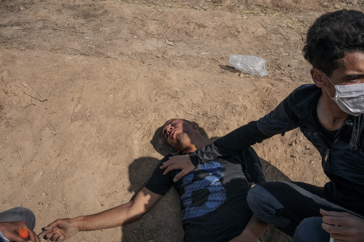 Gaza Strip, May 2018 - A Palestining with breathing problems after Israeli troops fired tear gas along the Gaza-Israel border.>< Striscia di Gaza, maggio 2018 - Un ragazzo palestinese è steso a terra dopo aver respirato i gas lacrimogeni lanciati dai soldati israeliani.