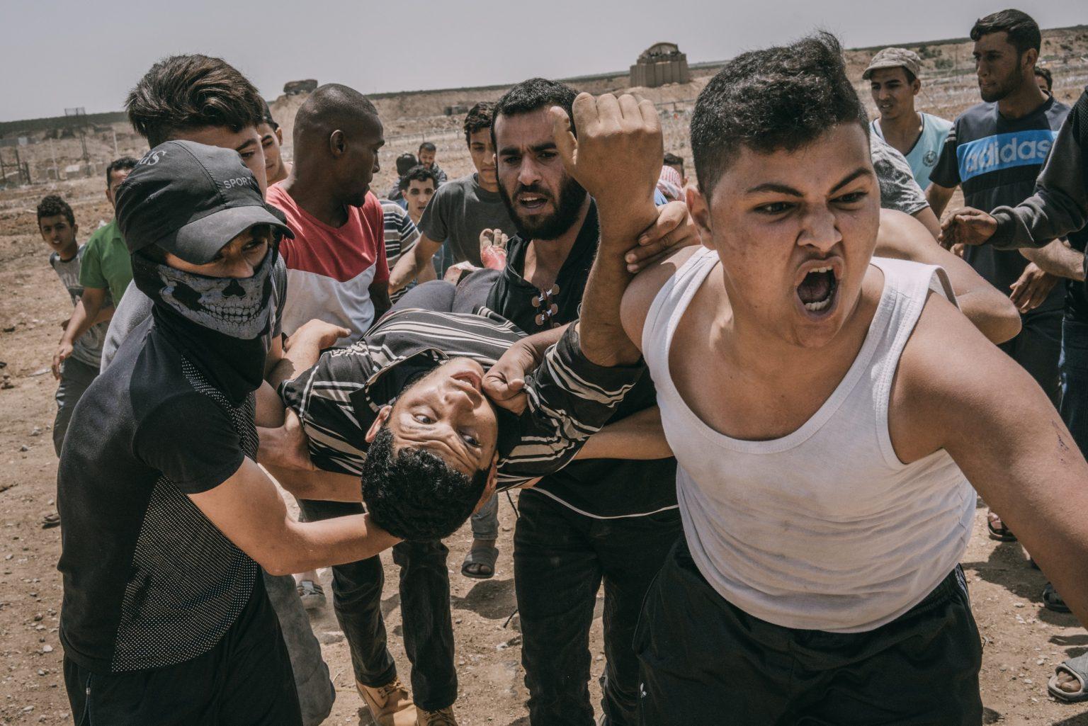 Gaza Strip, May 2018 - A wounded demonstrator is evacuated during the protest along the Gaza-Israel border. >< Striscia di Gaza, maggio 2018 - Un manifestante ferito viene portato via dal confine tra Gaza e Israele.