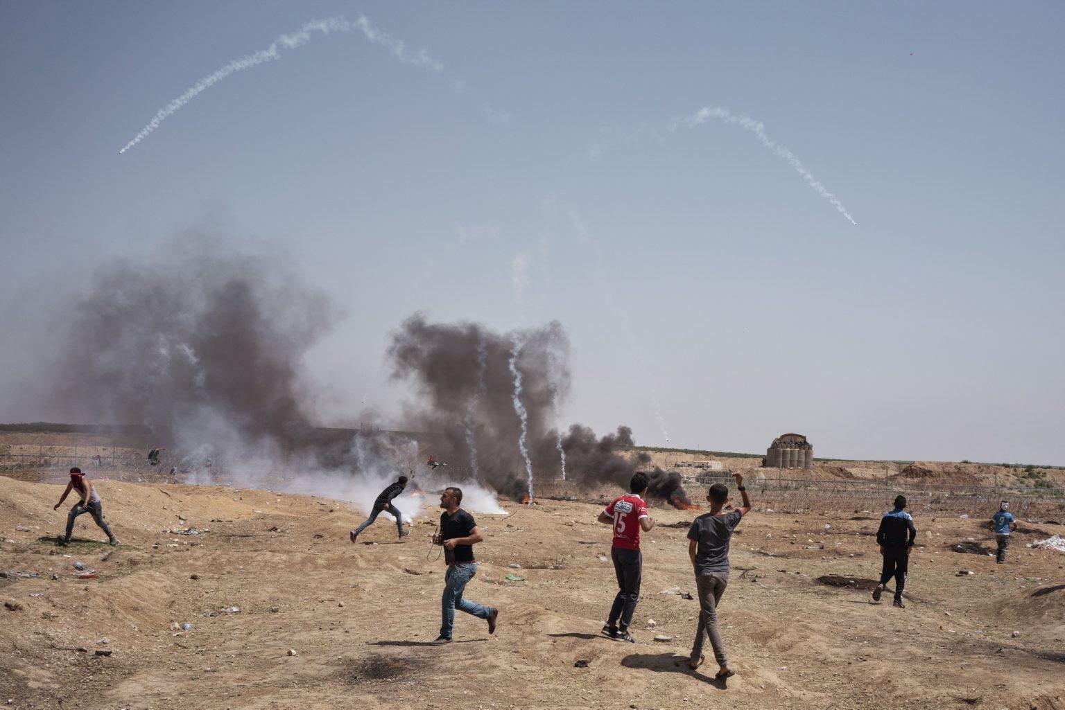 Gaza Strip, May 2018 - Tear gas are fired at Palestinian demonstrators by Israeli forces. >< Striscia di Gaza, maggio 2018 - Soldati israeliani lanciano gas lacrimogeni verdo i manifestanti palestinesi.