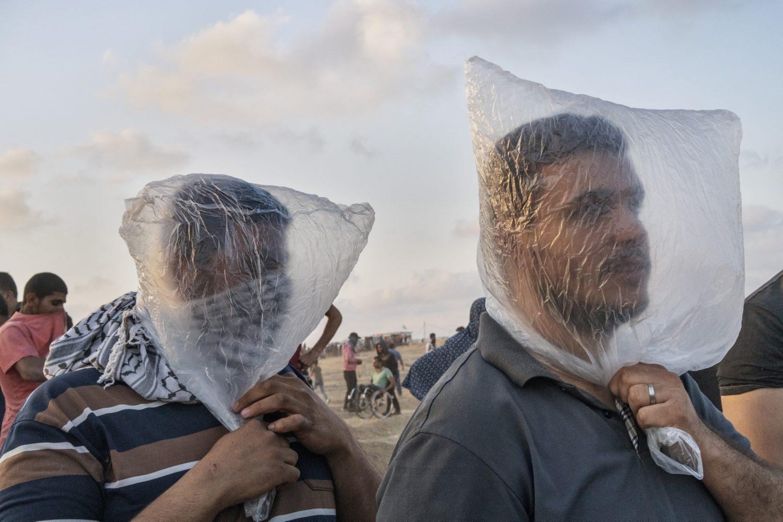 Gaza Strip, May 2018 - Two Palestinian men use a plastic bag to cover their face after Israeli troops fired tear gas along the Gaza-Israel border. >< Striscia di Gaza, maggio 2018 - Due uomini palestinesi usano delle buste di plastica per ripararsi dai gas lacrimogeni lanciati dai soldati israeliani.