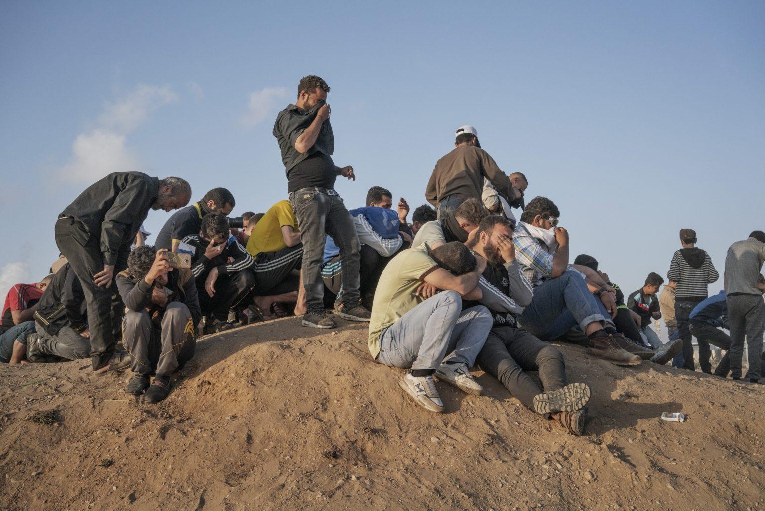 Gaza Strip, May 2018 - Palestinian cover their faces after Israeli forces fired tear gas along the Gaza-Israel border. >< Striscia di Gaza, maggio 2018 - Palestinesi si riparano il viso dai gas lacrimogeni lanciati dai soldati israeliani.