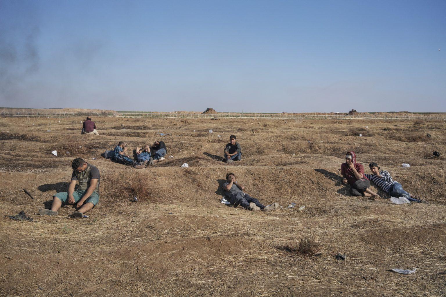 Gaza Strip, May 2018 - Palestinians sit along the Gaza-Israel border as smoke wafts in the distance. >< Striscia di Gaza, maggio 2018 - Palestinesi appostati lungo il confine tra Gaza e Israele mentre il fumo si alza in lontananza.