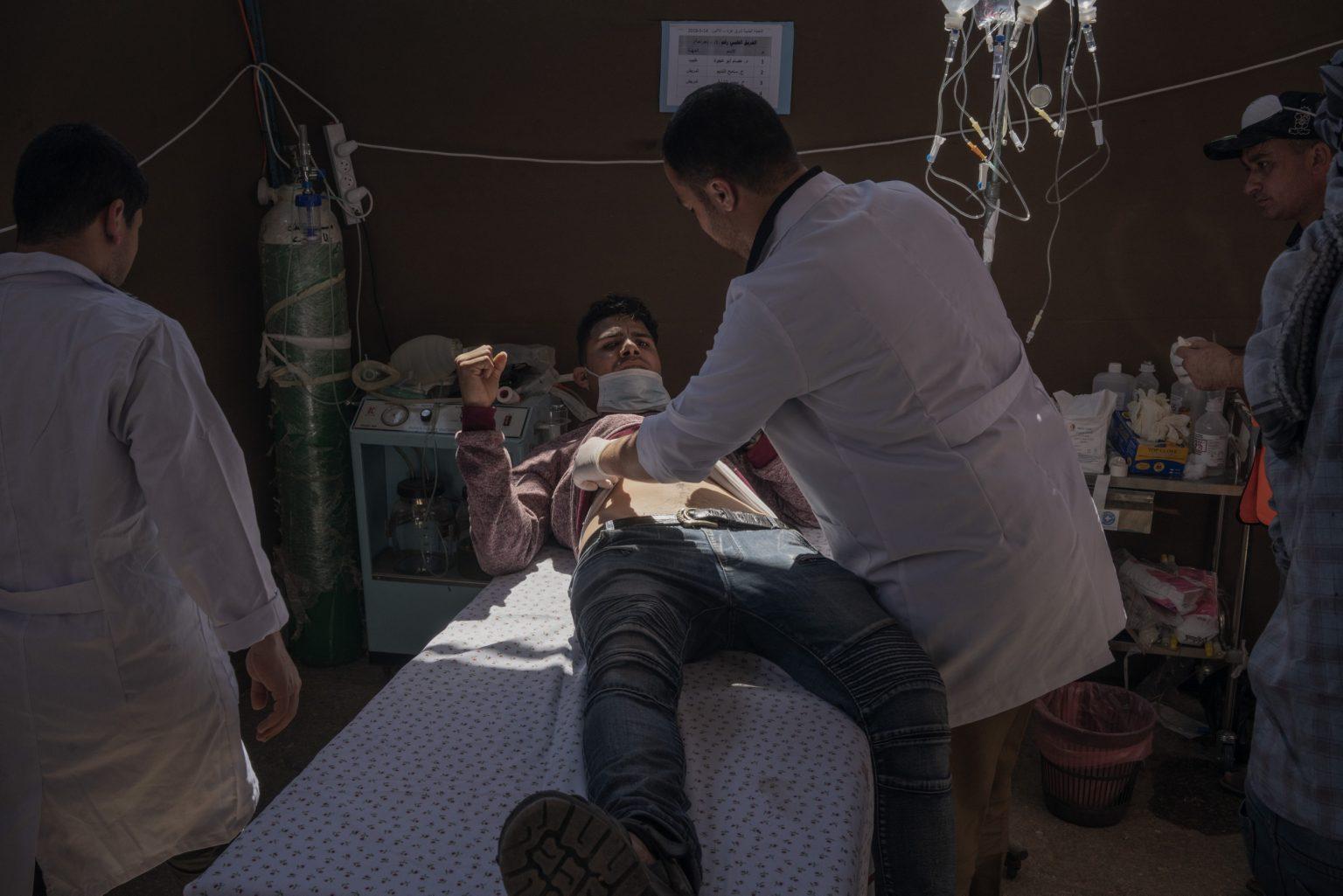 Gaza Strip, May 2018 - A man injured during the protest is assisted by medics in a field hospital set up along the Gaza-Israel border. >< Striscia di Gaza, maggio 2018 - Un ragazzo ferito durante le proteste viene asisstito dai dottori in un ospedale da campo lungo il confine tra Gaza e Israele.
