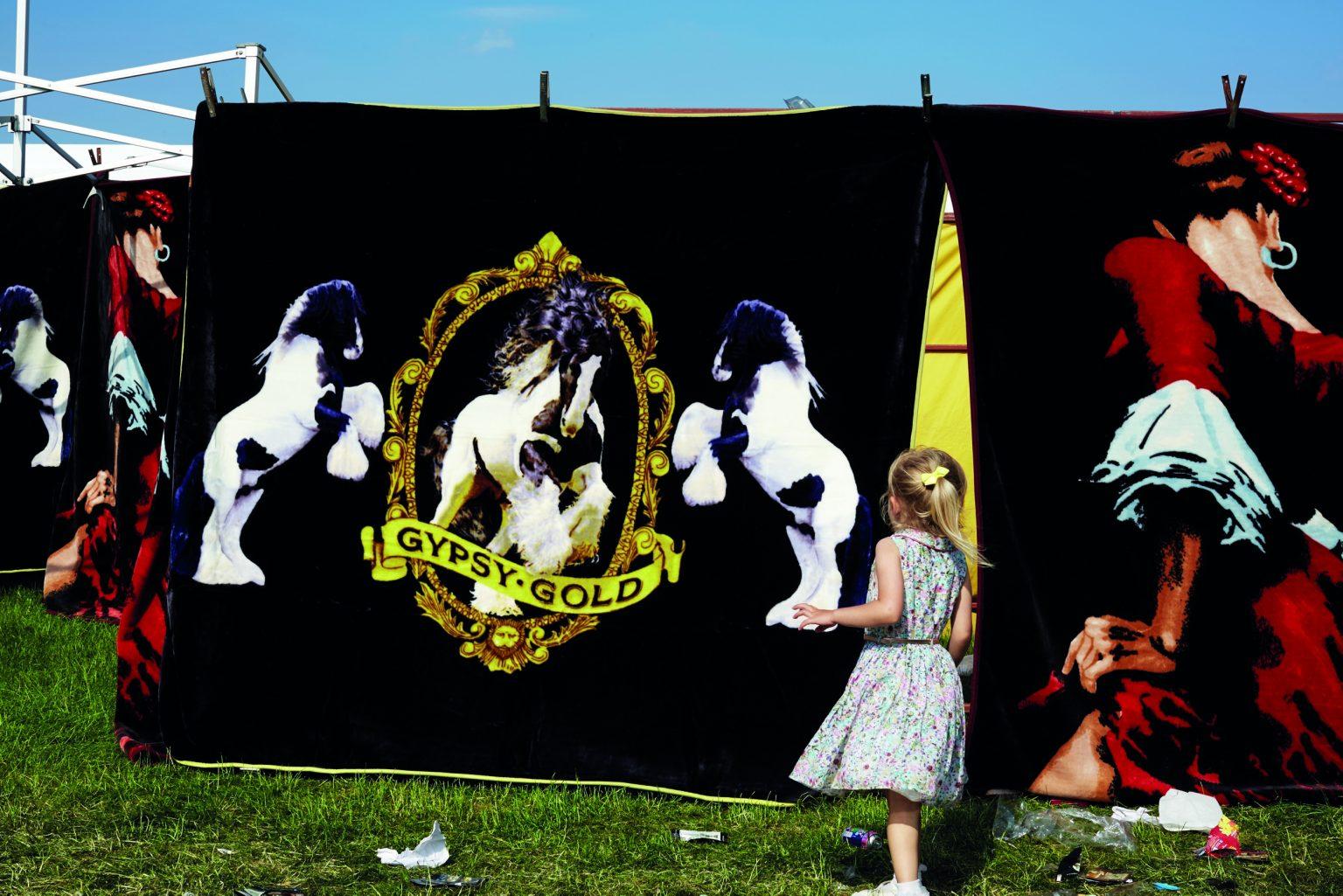 Appleby, United Kingdom, June 2016 - Appleby Horse Fair. Little gypsy girl playing with rugs in the parking lot market. ><  Appleby, Regno Unito, giugno 2016 - Appleby Horse Fair. Una bambina gitana gioca con dei tappeti nel parcheggio del negozio. *** Local Caption ***