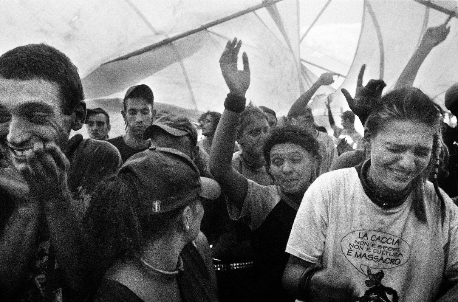 """Petriolo Terme, Marche, 2003 - Sandstorm during the summer party, Ferragosto holiday. Rave parties are usually organized by """"Tribes"""", groups of at least a dozen people. The tribes were always coming to Italy during the summer, cause the police was less strict, but above all to enjoy the great weather and the amazing locations. >< Petriolo Terme, Marche, 2003 - Tempesta di sabbia durante una festa estiva a Ferragosto. I rave party sono solitamente organizzati da """"tribù"""", gruppi di almeno una dozzina di persone. Le tribù venivano sempre in Italia durante l'estate, perché la polizia era meno severa, ma soprattutto per godersi il bel tempo e il panorama."""